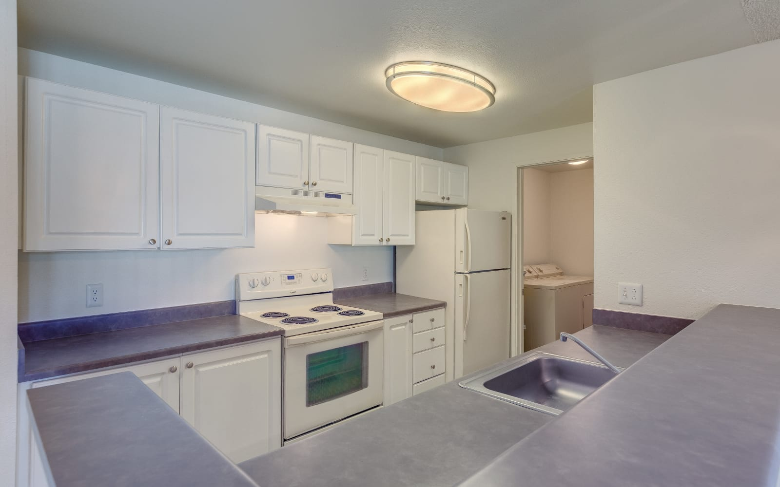 Kitchen featuring white finishes at Alaire Apartments in Renton, Washington