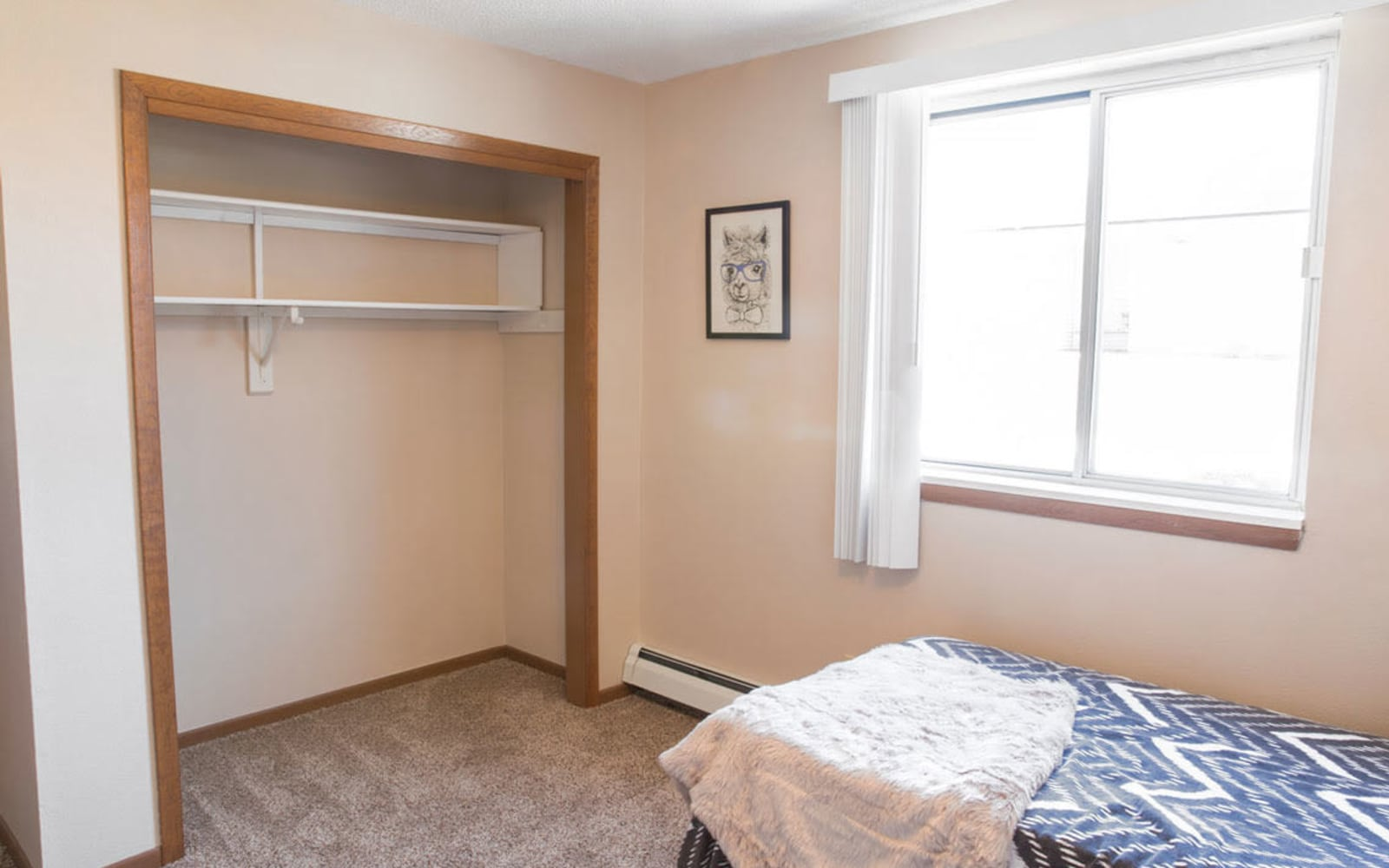 Bedroom with shelving in the closet at Campus View & Kirkwood Court in Cedar Rapids, Iowa