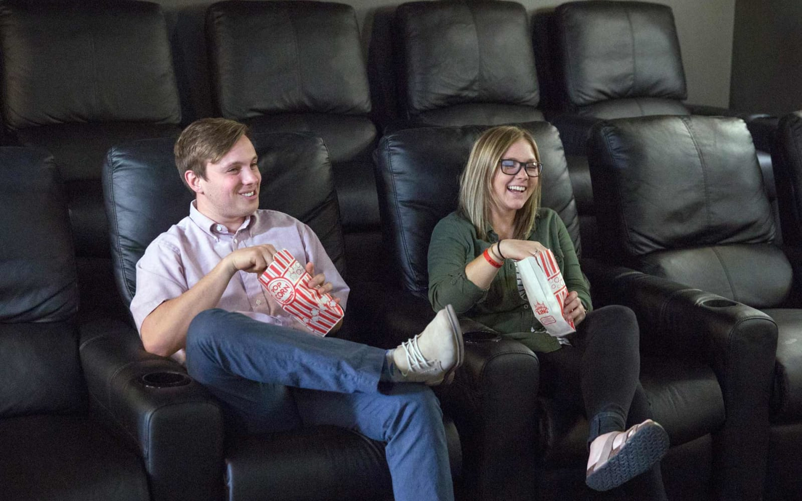 Two residents enjoying a movie in the theater at Prairie Pointe Student Living in Ankeny, Iowa