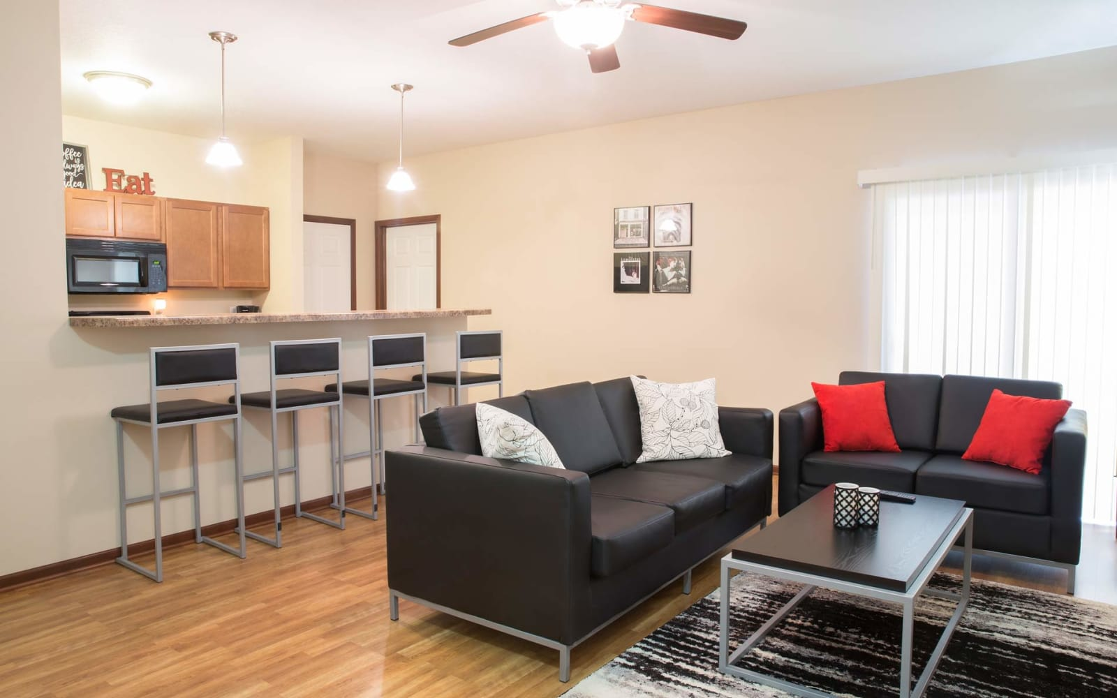 The kitchen leads to bar seating and the living room at Prairie Pointe Student Living in Ankeny, Iowa