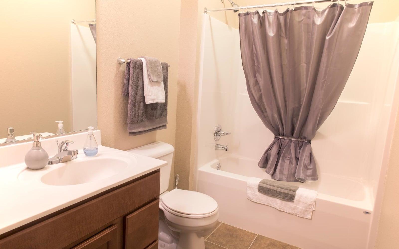 An apartment bathroom with a bathtub at Prairie Pointe Student Living in Ankeny, Iowa