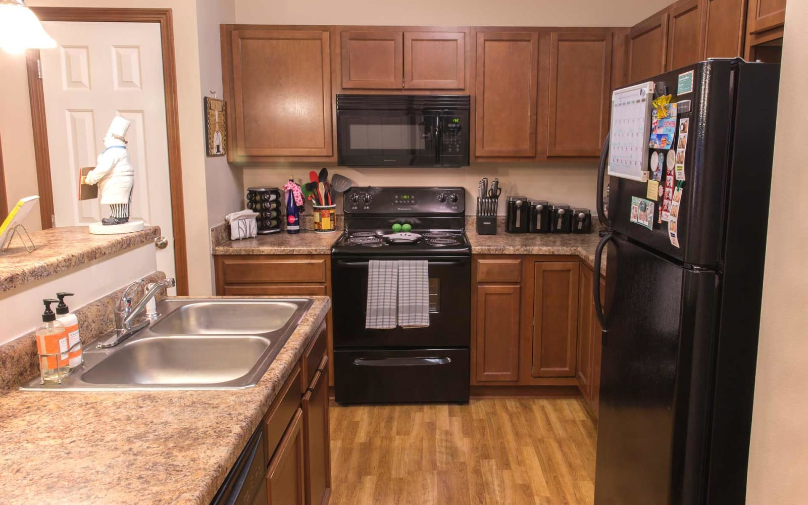 An apartment kitchen with a sink in the island at Providence Pointe in Johnston, Iowa