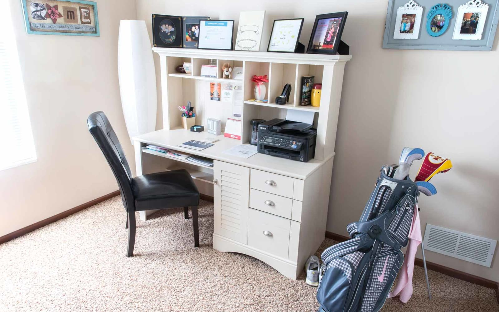 A desk with golf clubs next to it at Providence Pointe in Johnston, Iowa