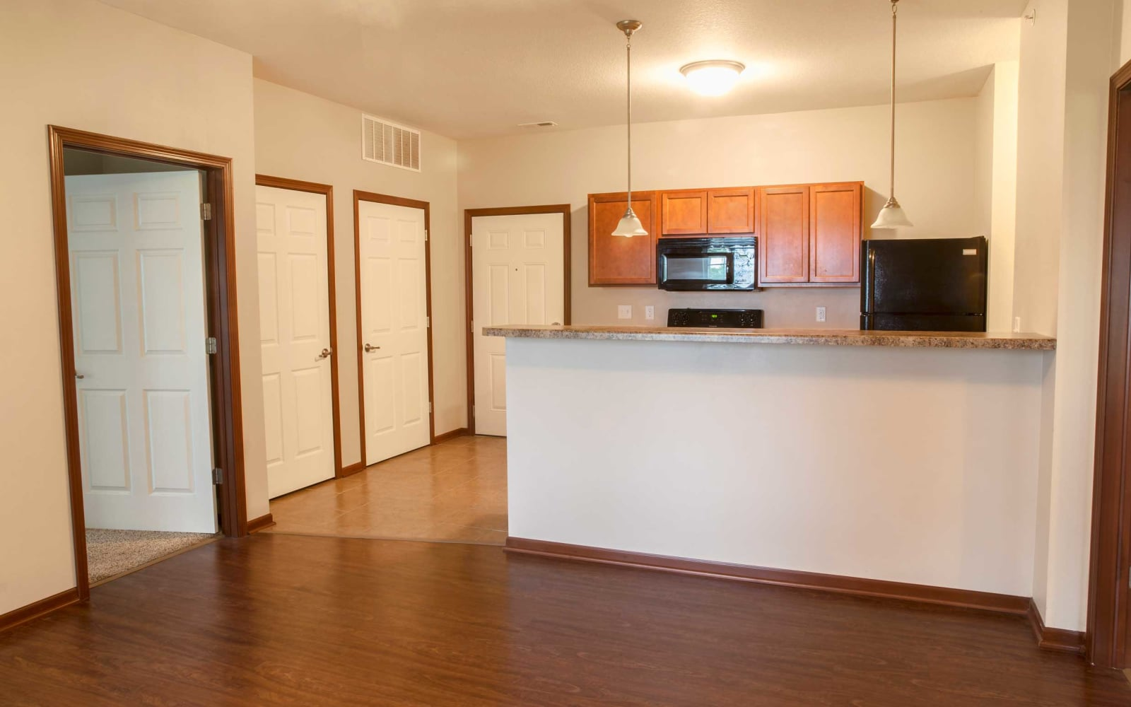 Kitchen with bar seating and doors to bedrooms at Westwood Village in Ames, Iowa