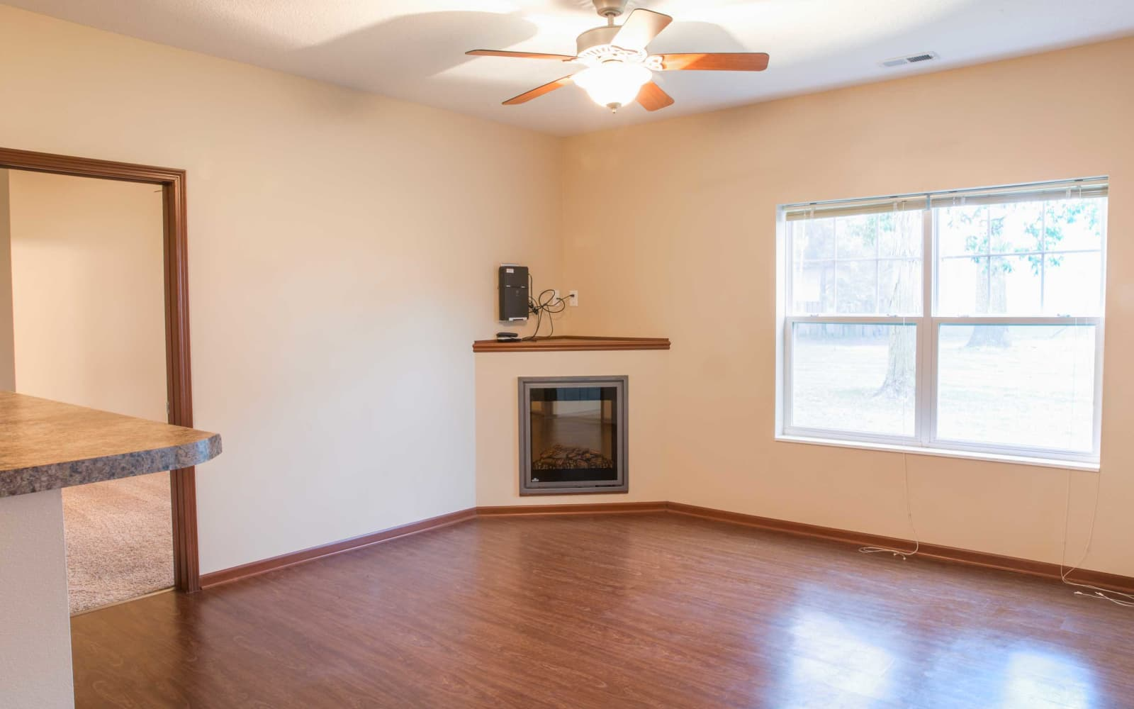 Living room with wood flooring and a fireplace at Westwood Village in Ames, Iowa