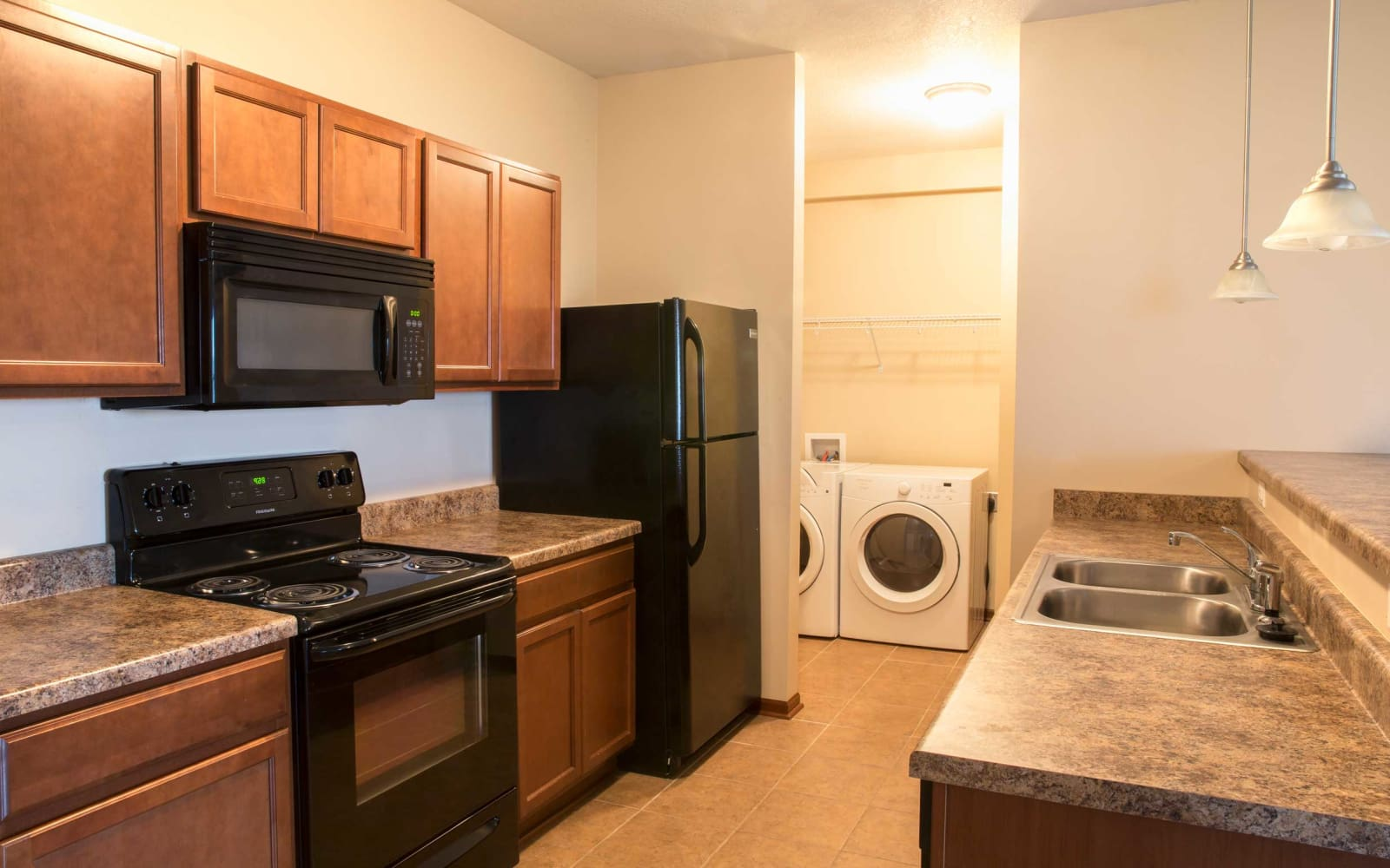 Apartment kitchen and adjacent laundry room= at Westwood Village in Ames, Iowa