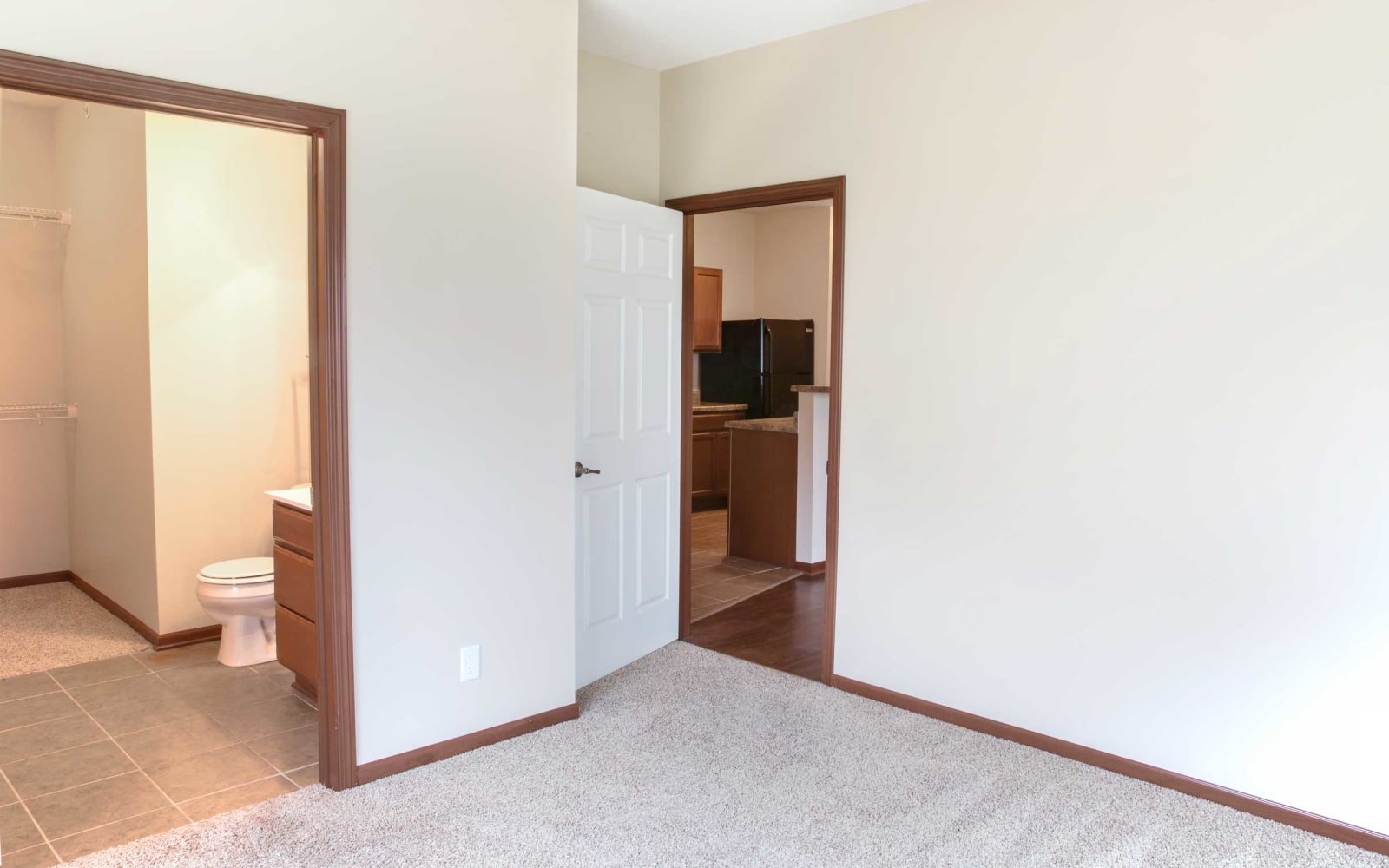 A bedroom to the left of the kitchen with an attached bathroom at Westwood Village in Ames, Iowa