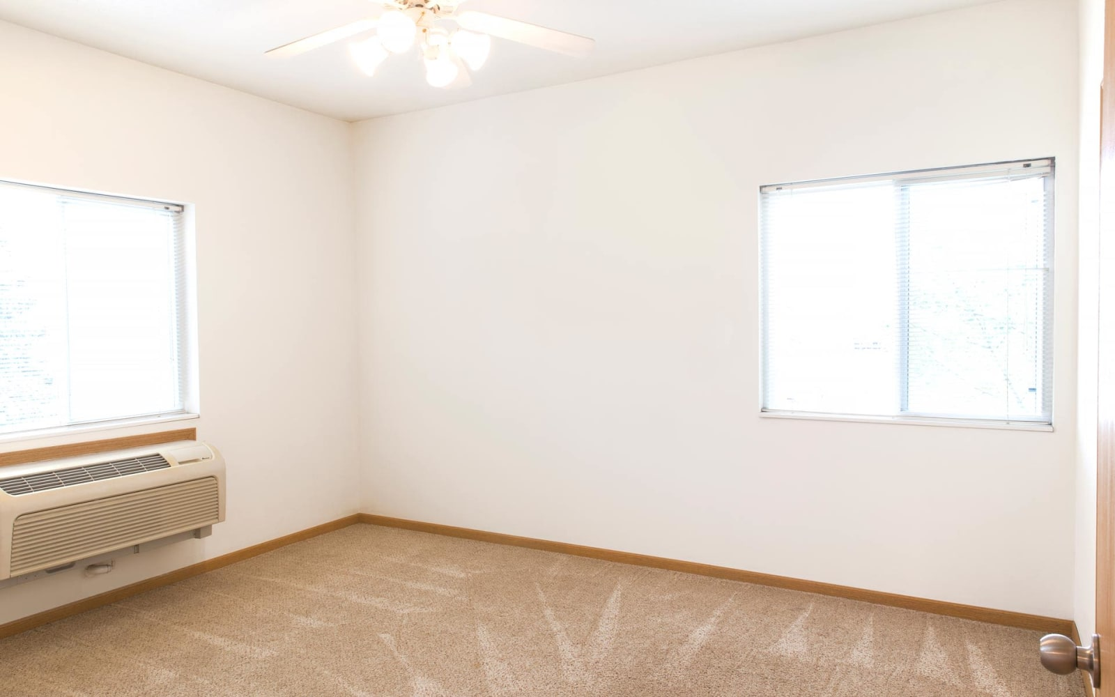 Bedroom with a ceiling fan and air conditioning at Westwood Village in Ames, Iowa