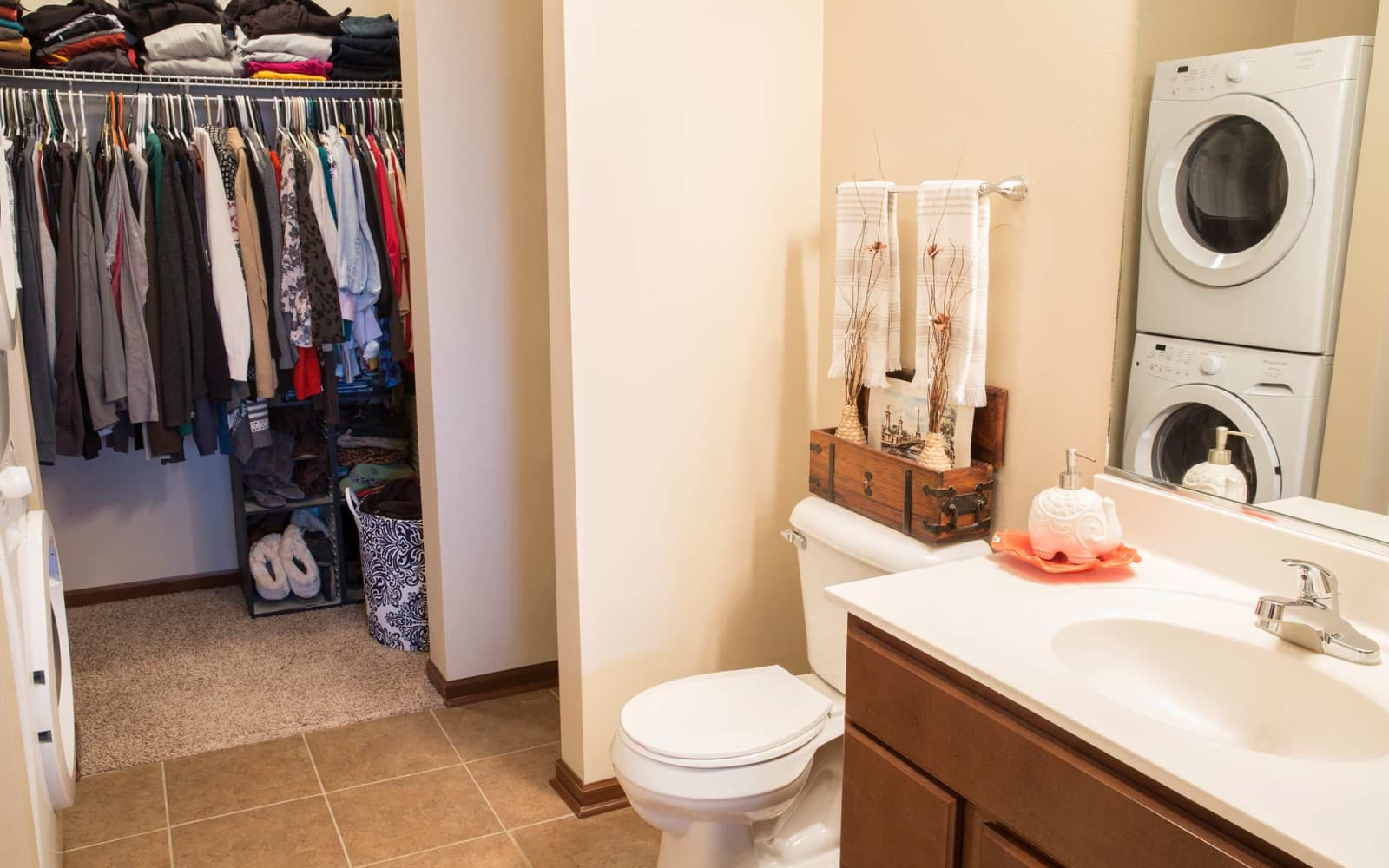 Bathroom with a stacked washer and dryer at Woodland Reserve in Ankeny, Iowa