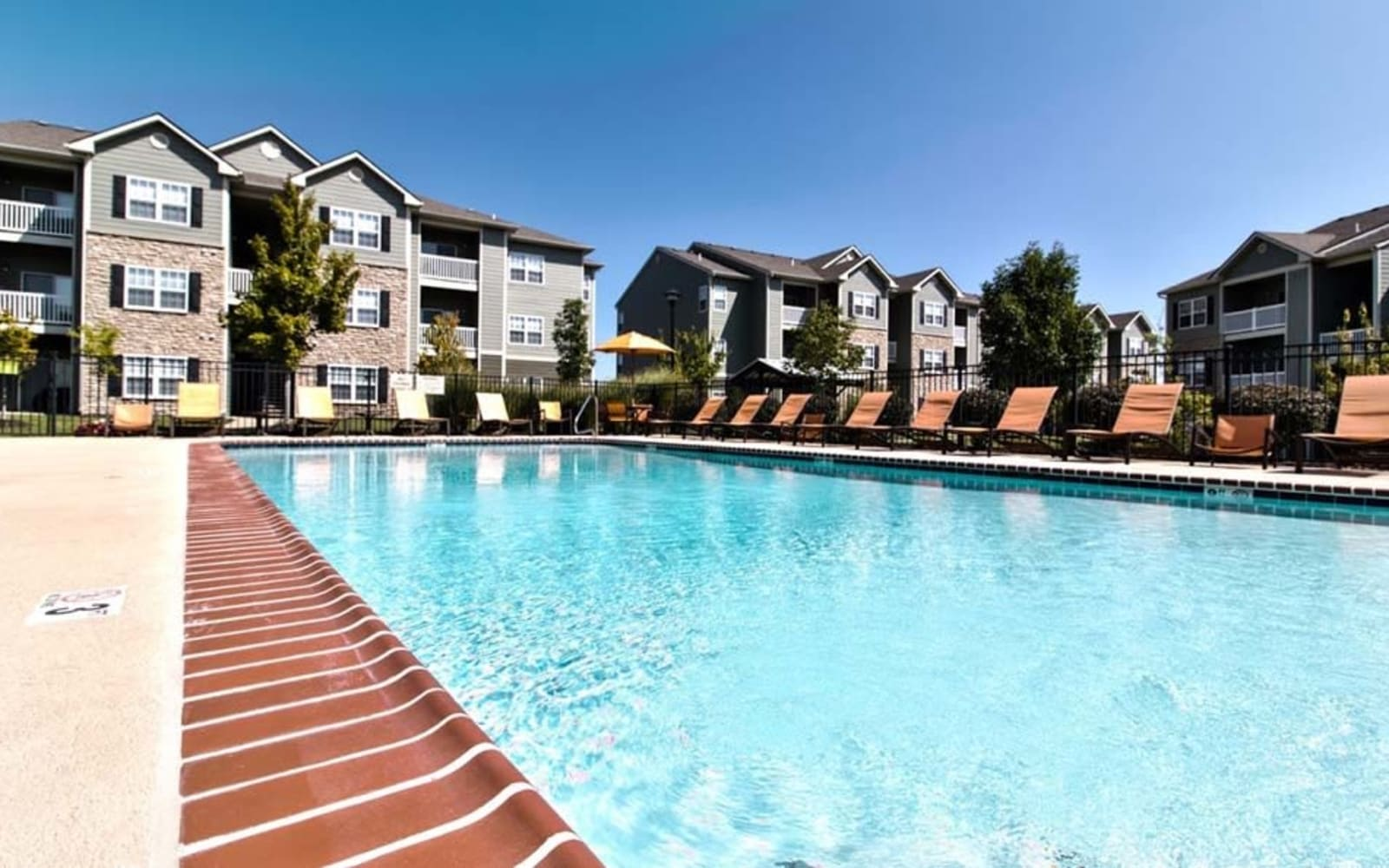 Resident pool with lounge chairs at Aventura at Richmond in Saint Peters, Missouri.