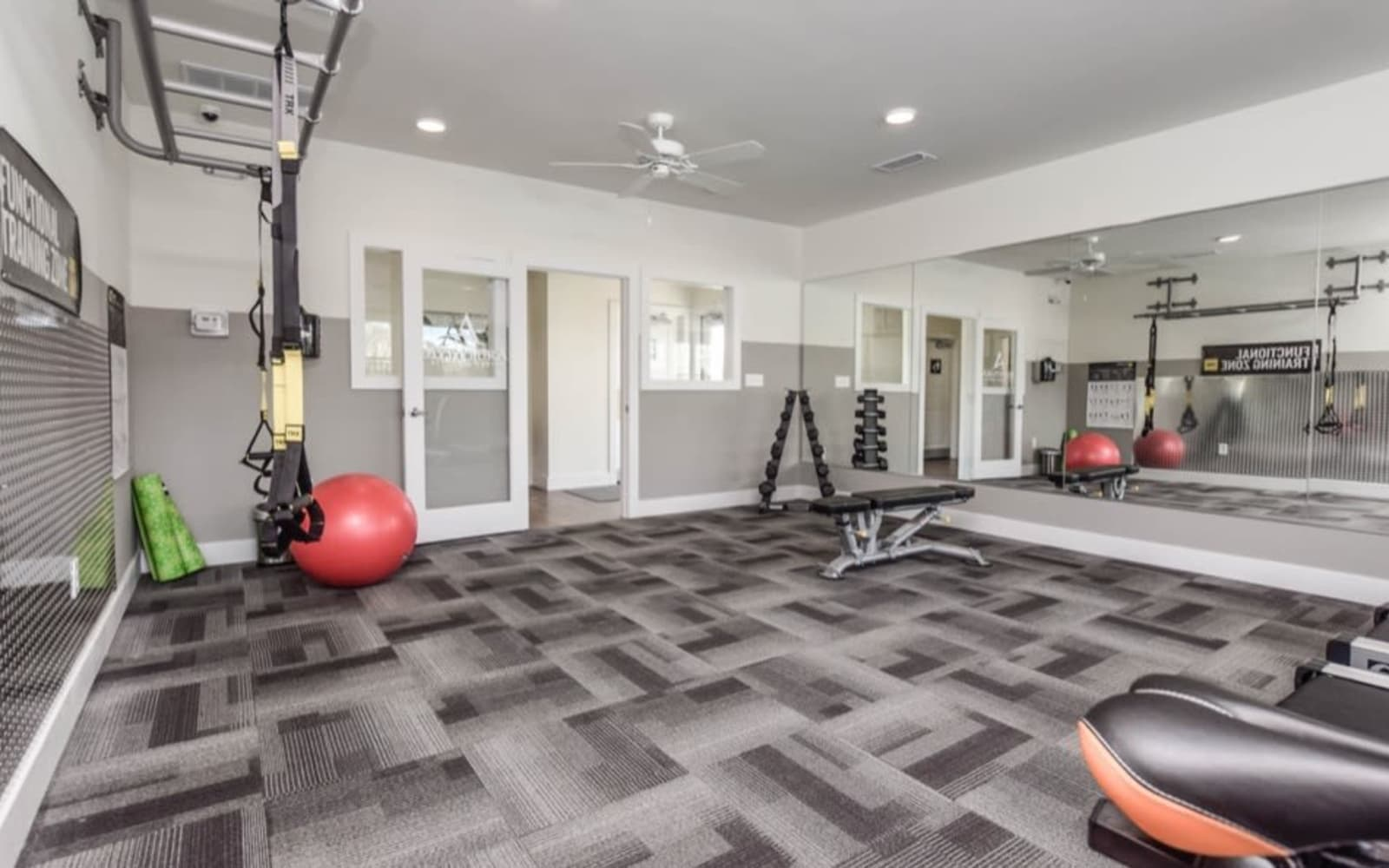 Resident fitness center with large mirrors at Aventura at Towne Centre in Ellisville, Missouri.