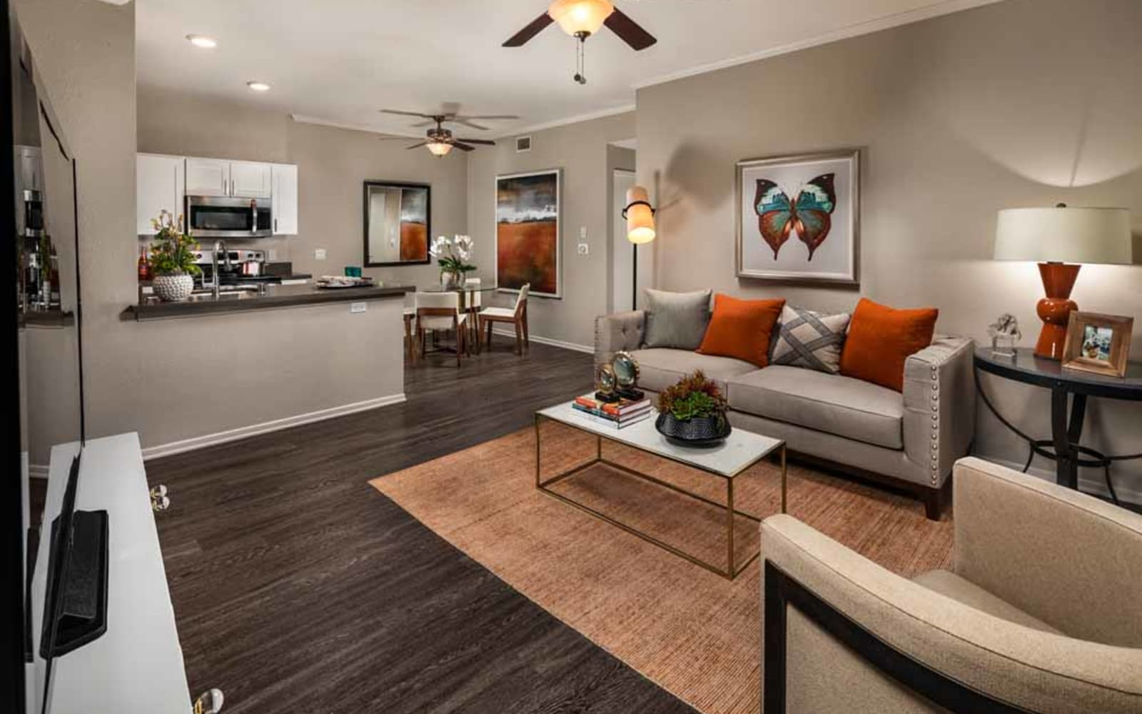 An apartment kitchen facing the living room at Colonnade at Sycamore Highlands in Riverside, California