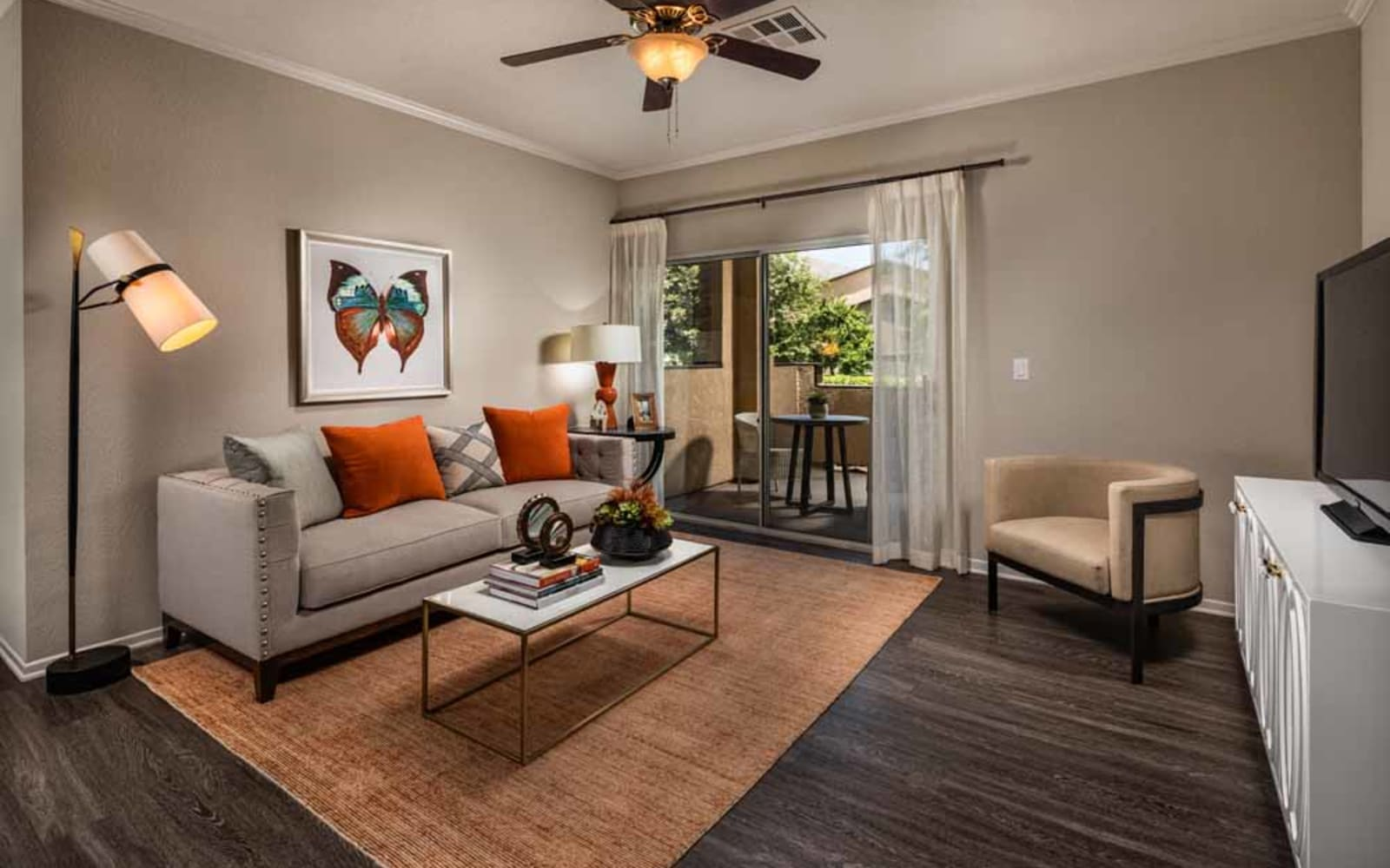 An apartment living room with a ceiling fan at Colonnade at Sycamore Highlands in Riverside, California