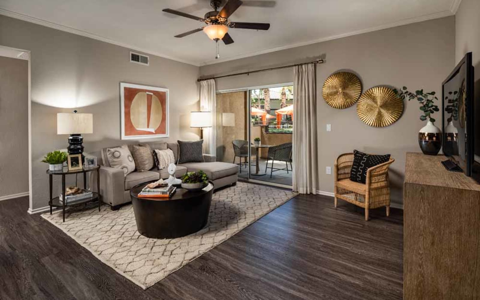 An apartment living room with sliding glass doors to the balcony at Colonnade at Sycamore Highlands in Riverside, California
