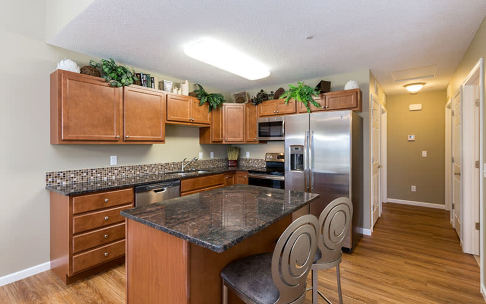 Wood flooring and granite counter tops in an apartment kitchen at The Landing of Clinton in Clinton, Iowa