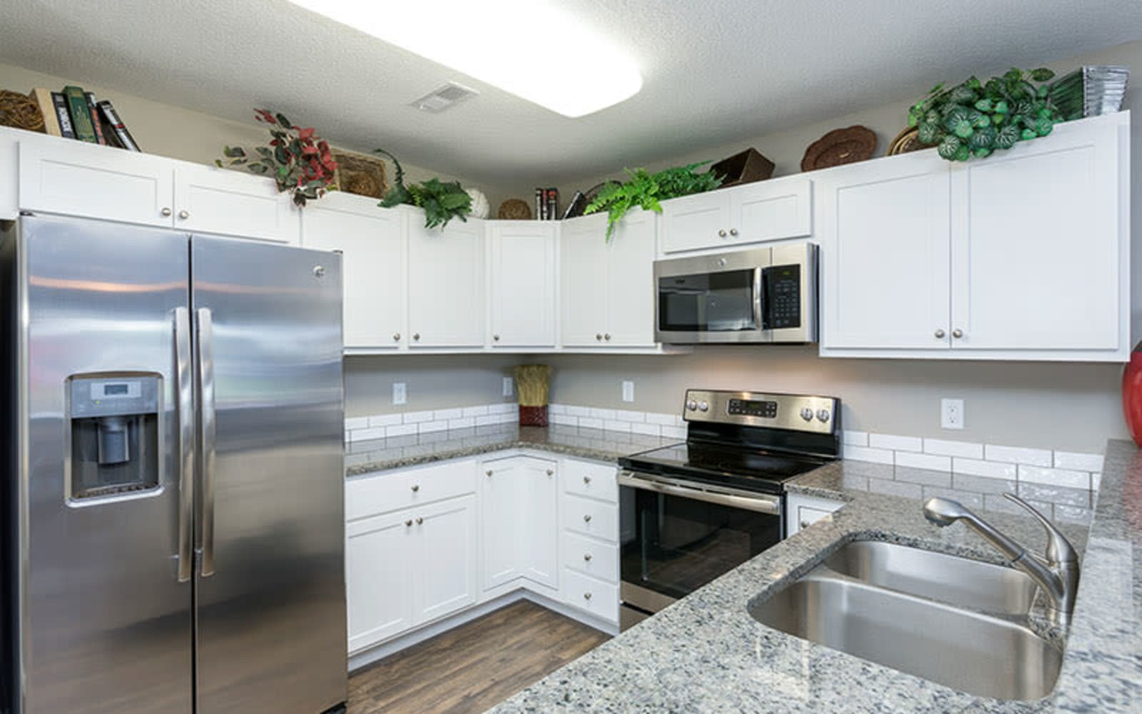 An apartment kitchen with white cabinets at The Landing of Clinton in Clinton, Iowa