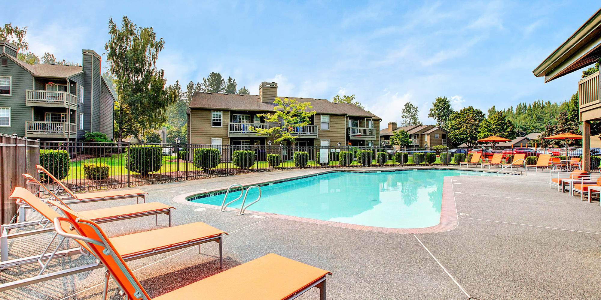 Beautiful pool area with lounge chairs at Waters Edge Apartments in Kent, WA