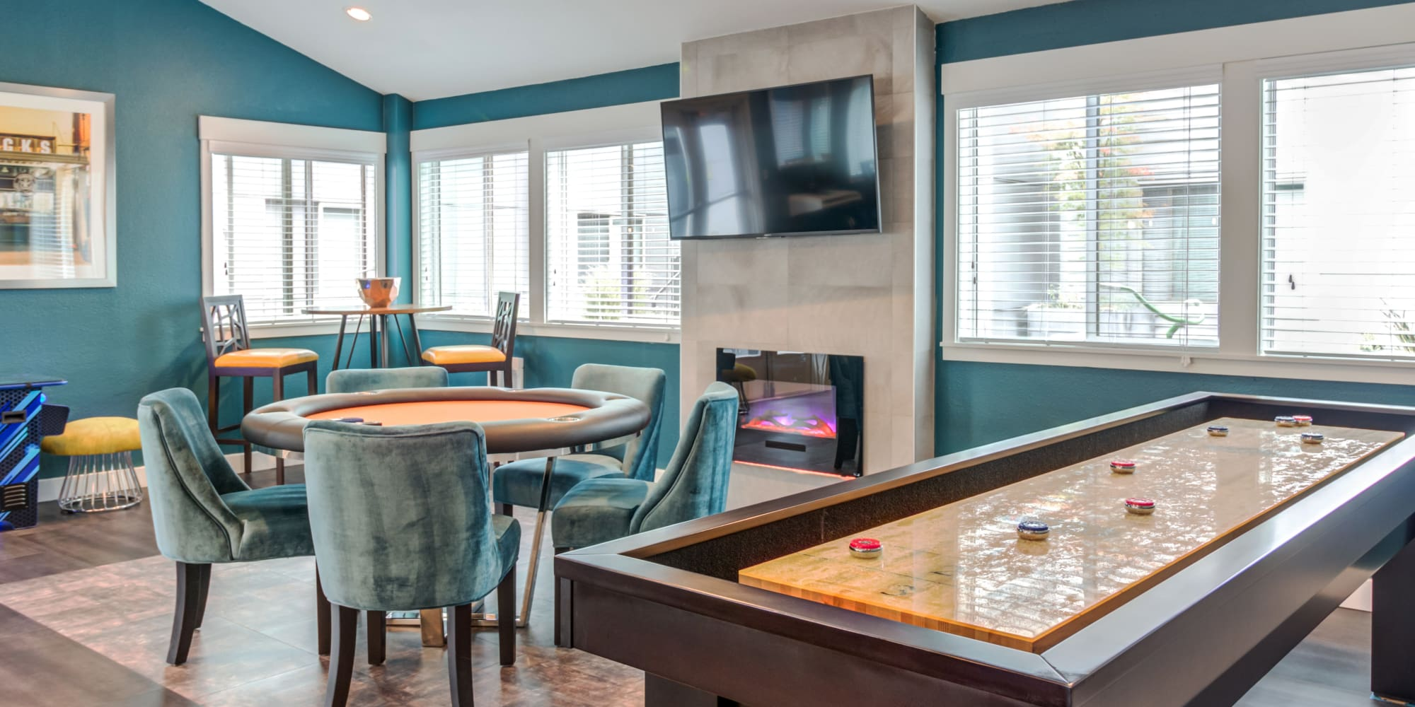 Resident Clubhouse game room with shuffleboard, TV, pac man machine and poker table in Seattle, WA