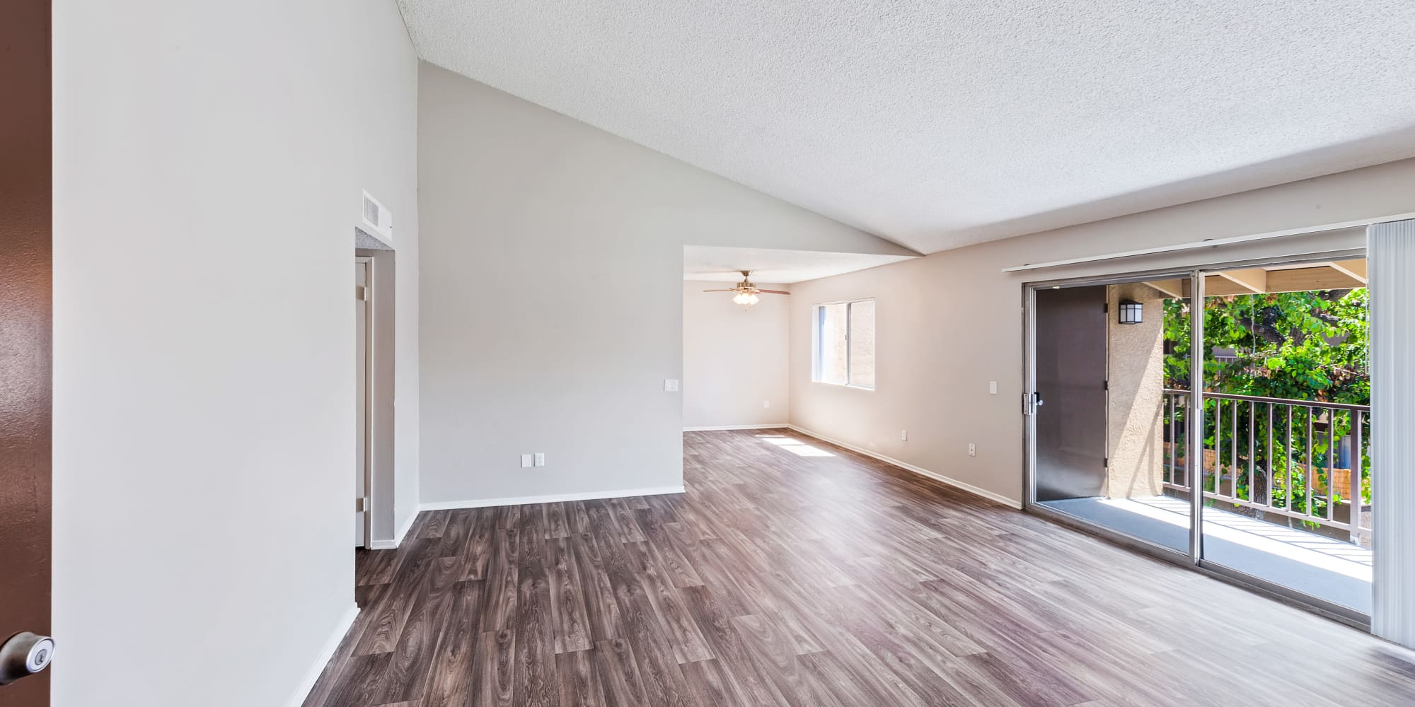 Spacious living room with patio access at West Fifth Apartments in Ontario, California