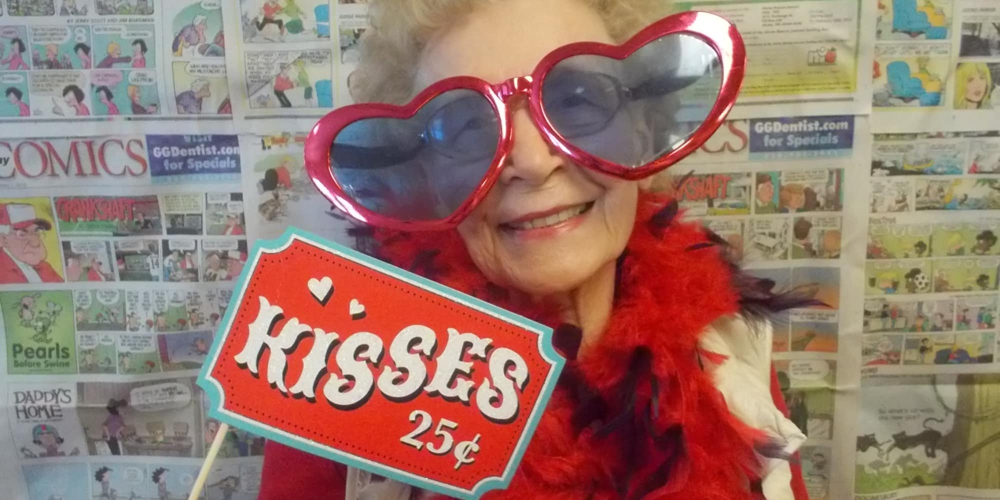 A resident with heart glasses and a kisses for twenty-five cents sign at Somerset Lodge in Gladstone, Oregon
