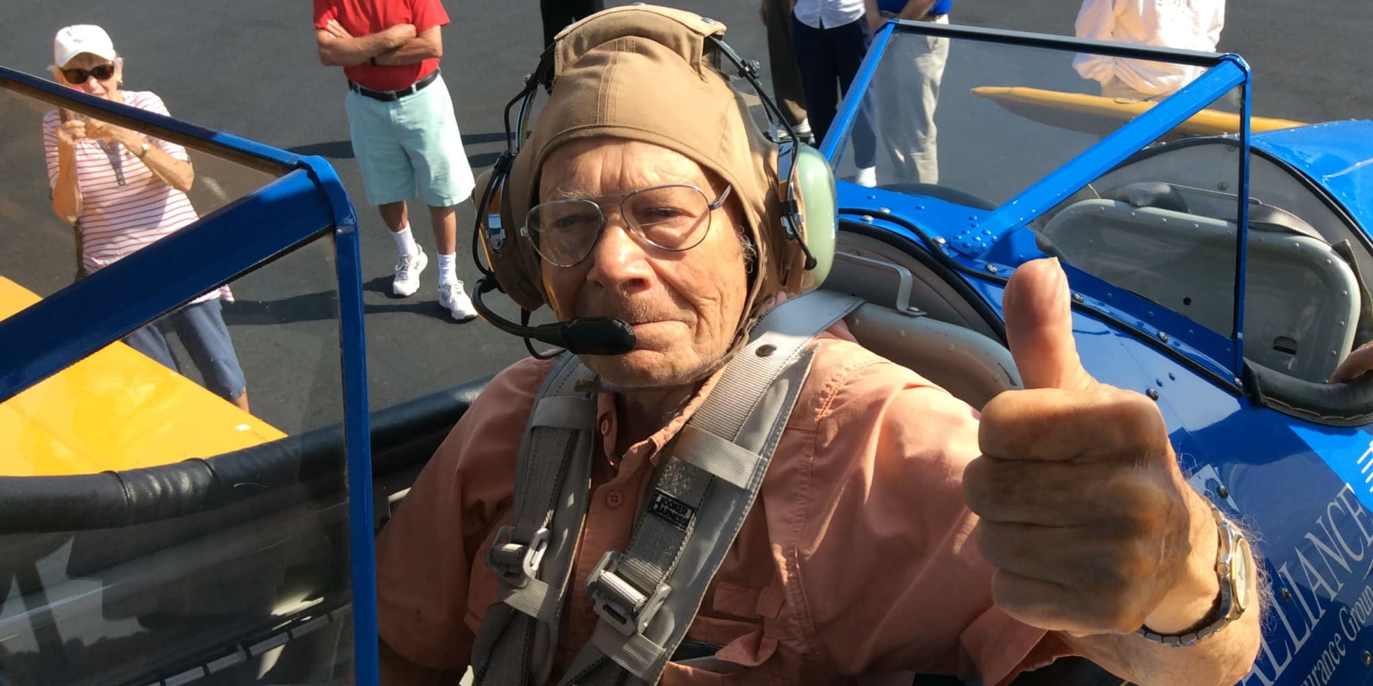 A resident from Southern Pines Gracious Retirement Living in Southern Pines, North Carolina giving a thumbs up from inside an airplane