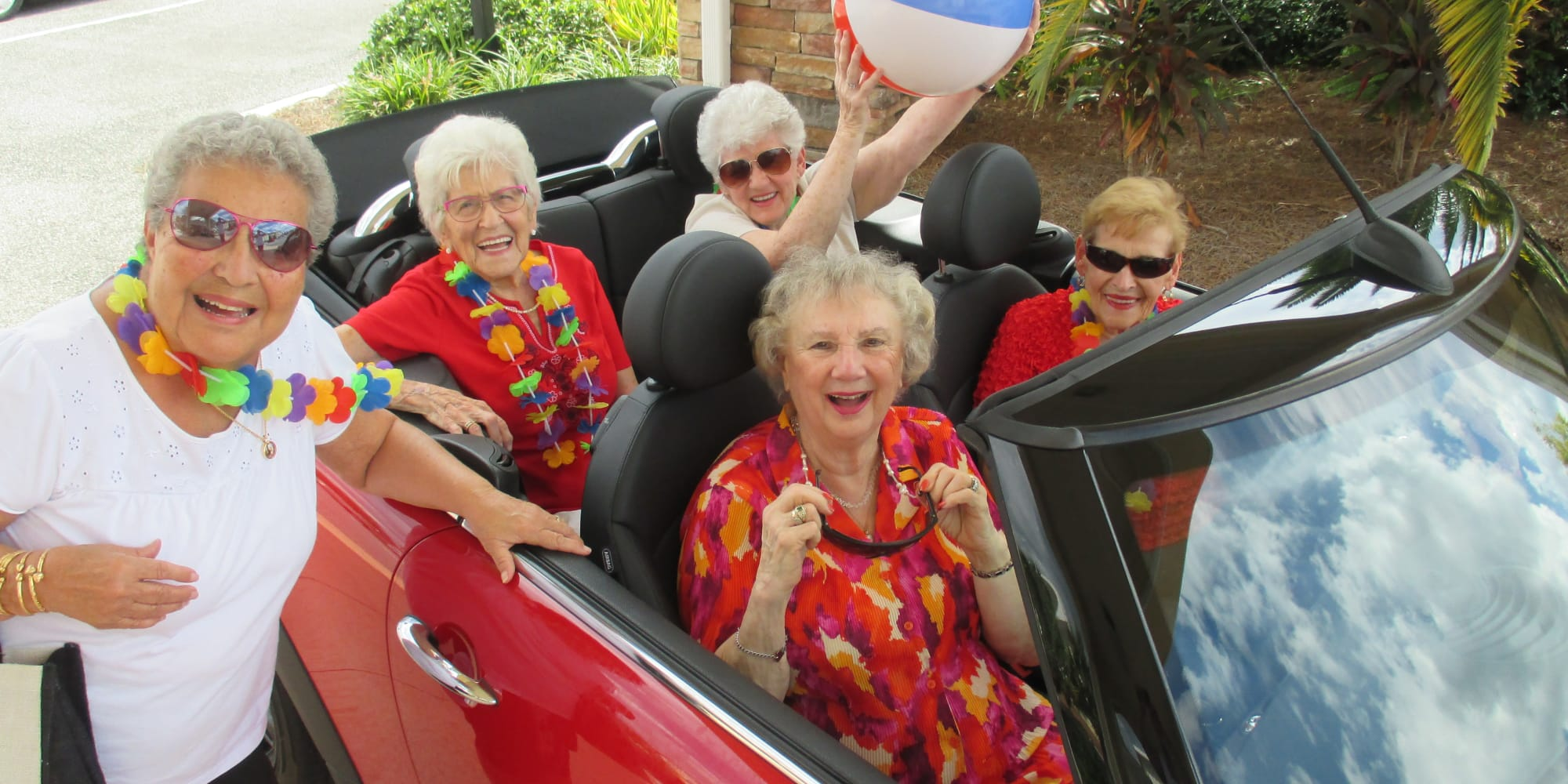Residents dressed in tropical clothing in a car at Steeplechase Retirement Residence in Oxford, Florida
