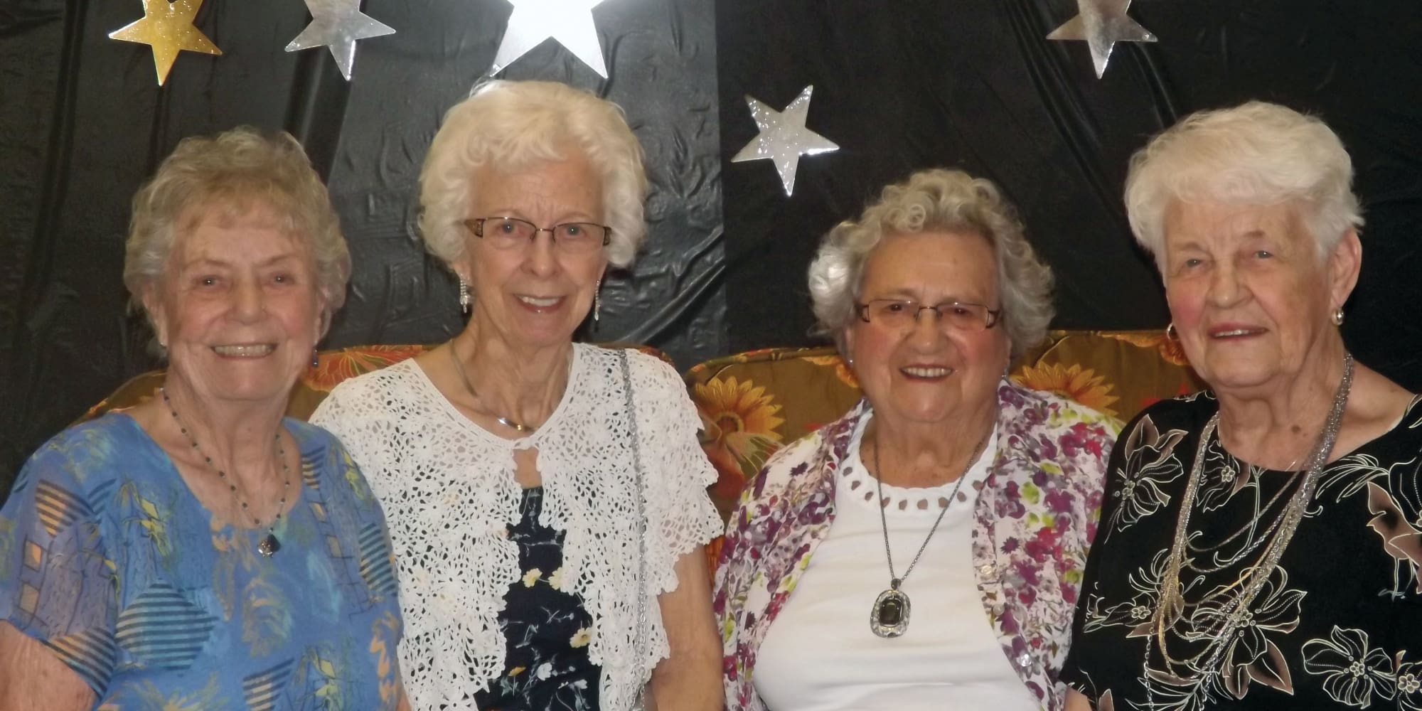 A group of residents posing in front of a backdrop at Sterling Heights Gracious Retirement Living in Bethlehem, Pennsylvania