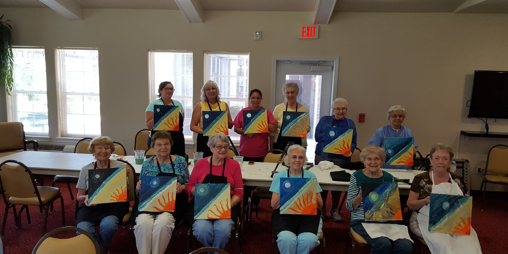 Residents holding their paintings at Summerville Estates Gracious Retirement Living in Summerville, South Carolina