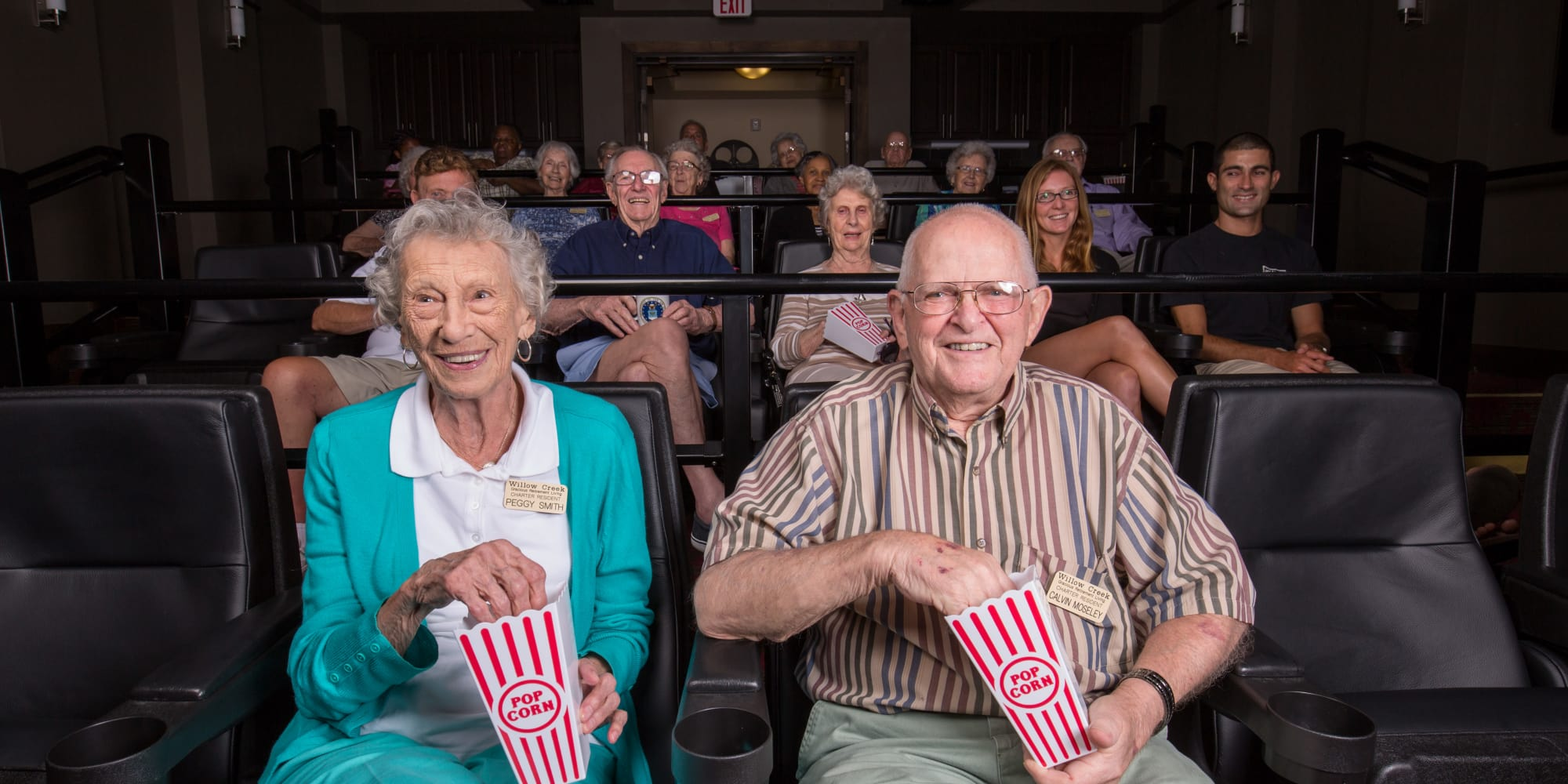 Residents eating popcorn and watching a movie at Willow Creek Gracious Retirement Living in Chesapeake, Virginia