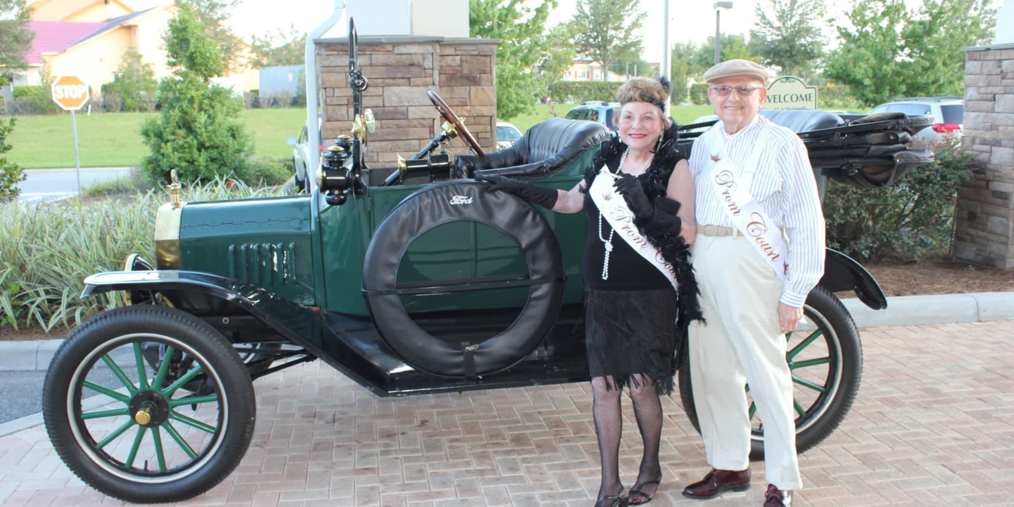 Prim king and queen posing in front of a classic car at Winterberry Heights Assisted Living in Bangor, Maine