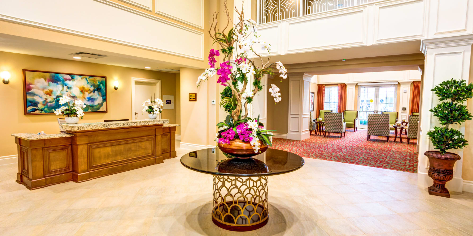 The Meridian at Boca Raton lobby with reception desk and center console table with large floral arrangement