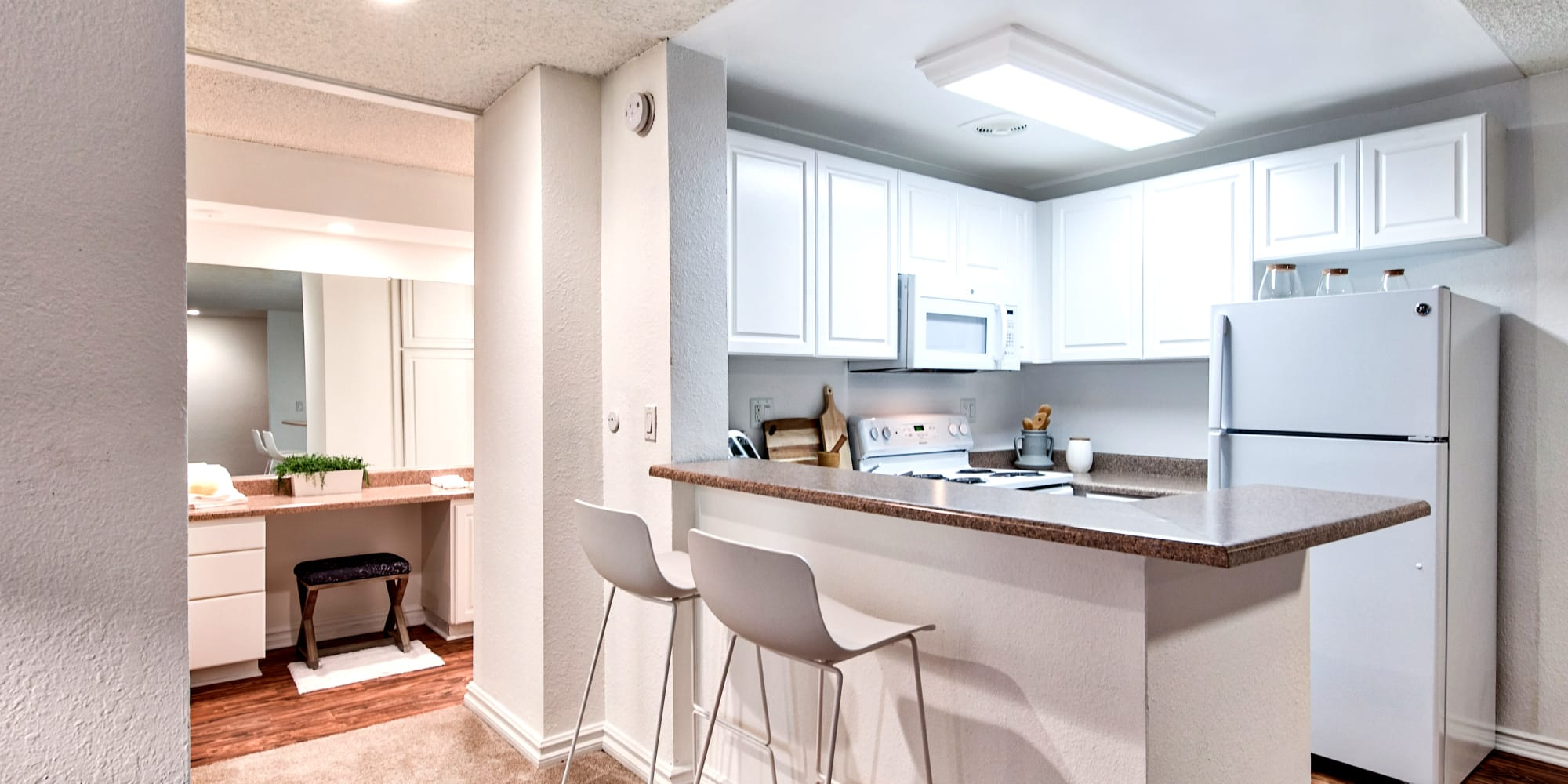 Kitchen with white appliances and cabinetry in a model home at The Meadows in Culver City, California