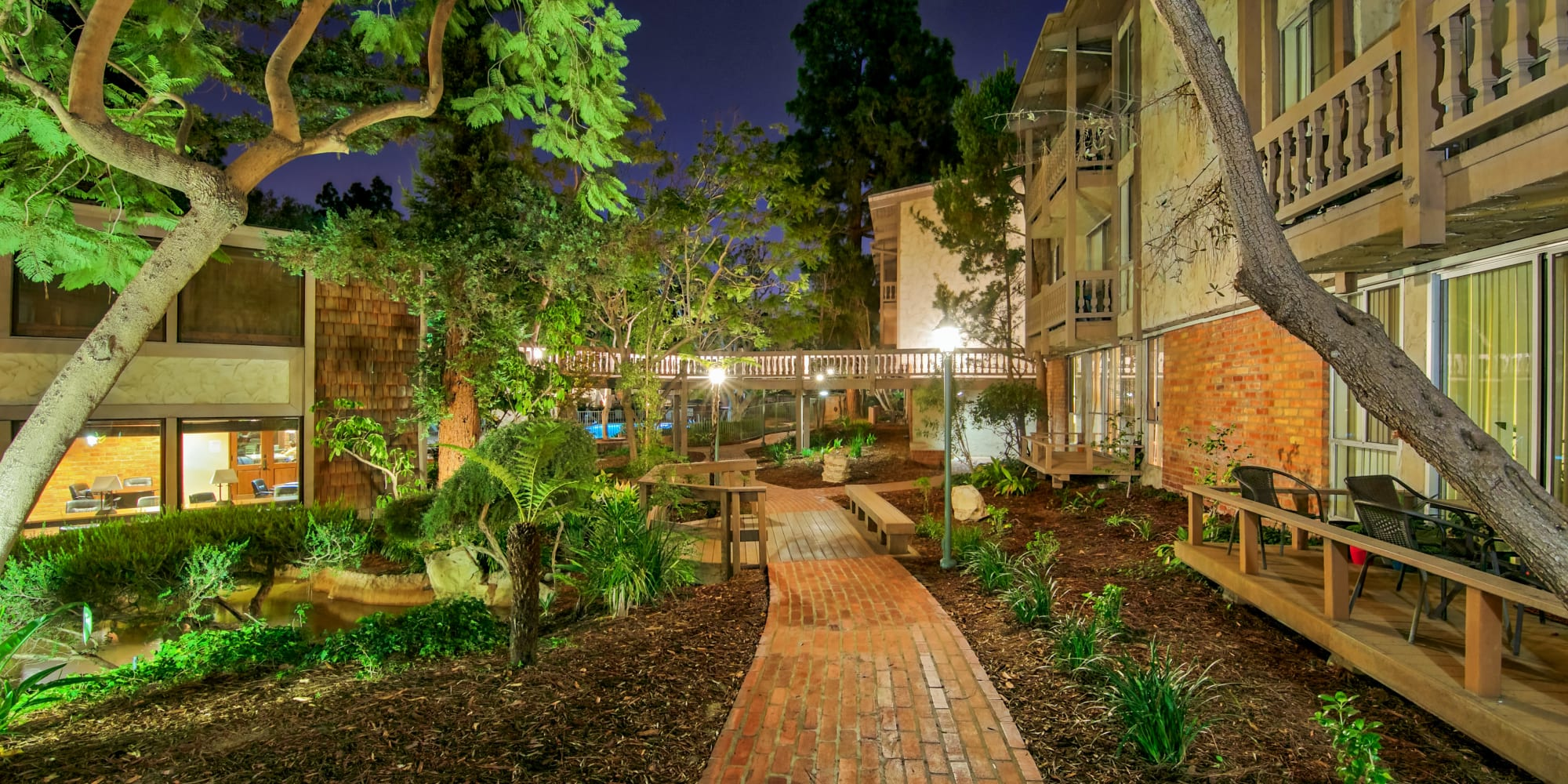 Brick walking path surrounded by lush landscaping between resident buildings at The Meadows in Culver City, California