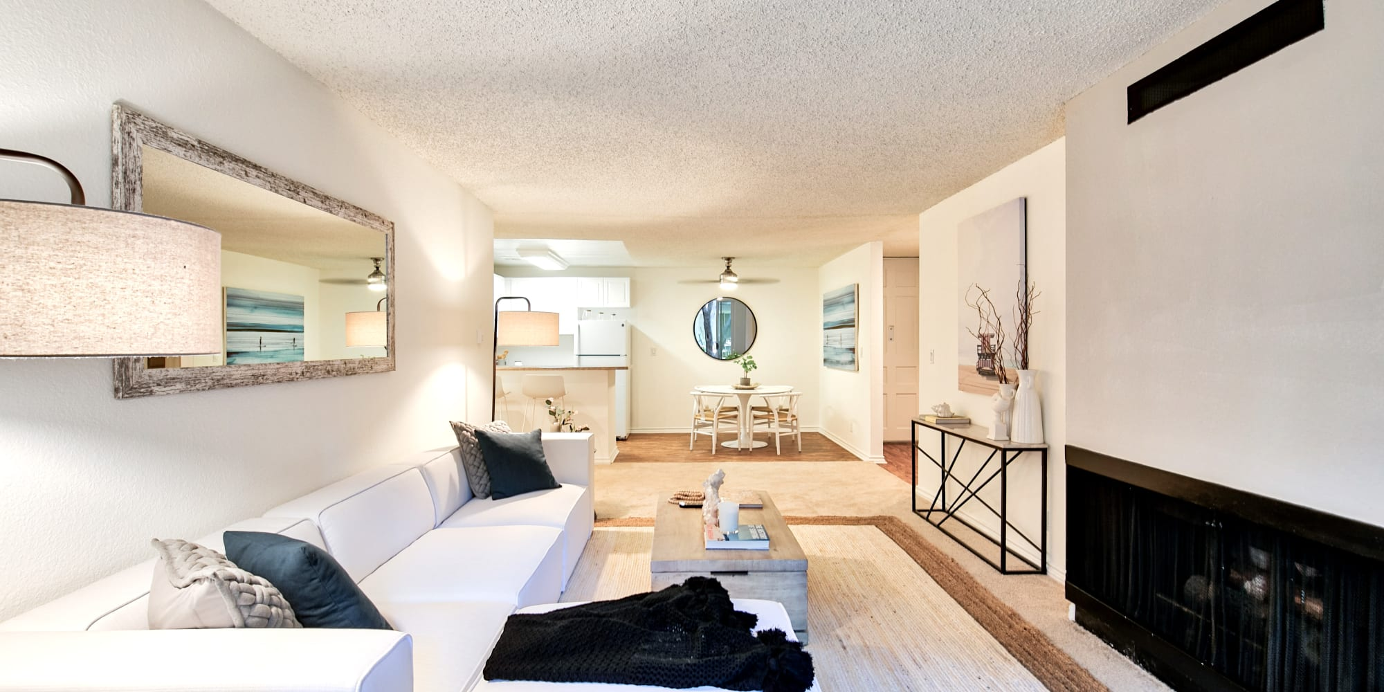 Spacious, well-furnished living room with wood-style flooring in a model home at The Meadows in Culver City, California