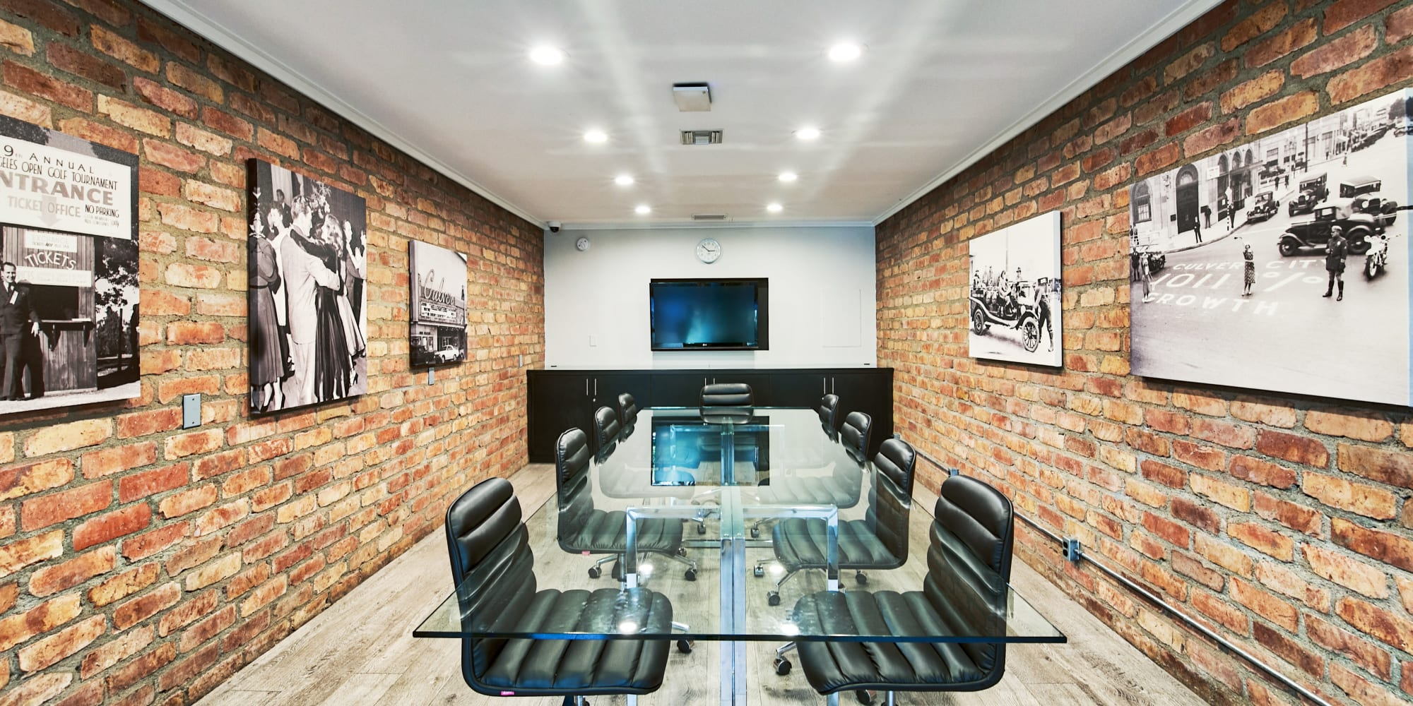 Business center meeting room with a large table and flatscreen TV at The Meadows in Culver City, California