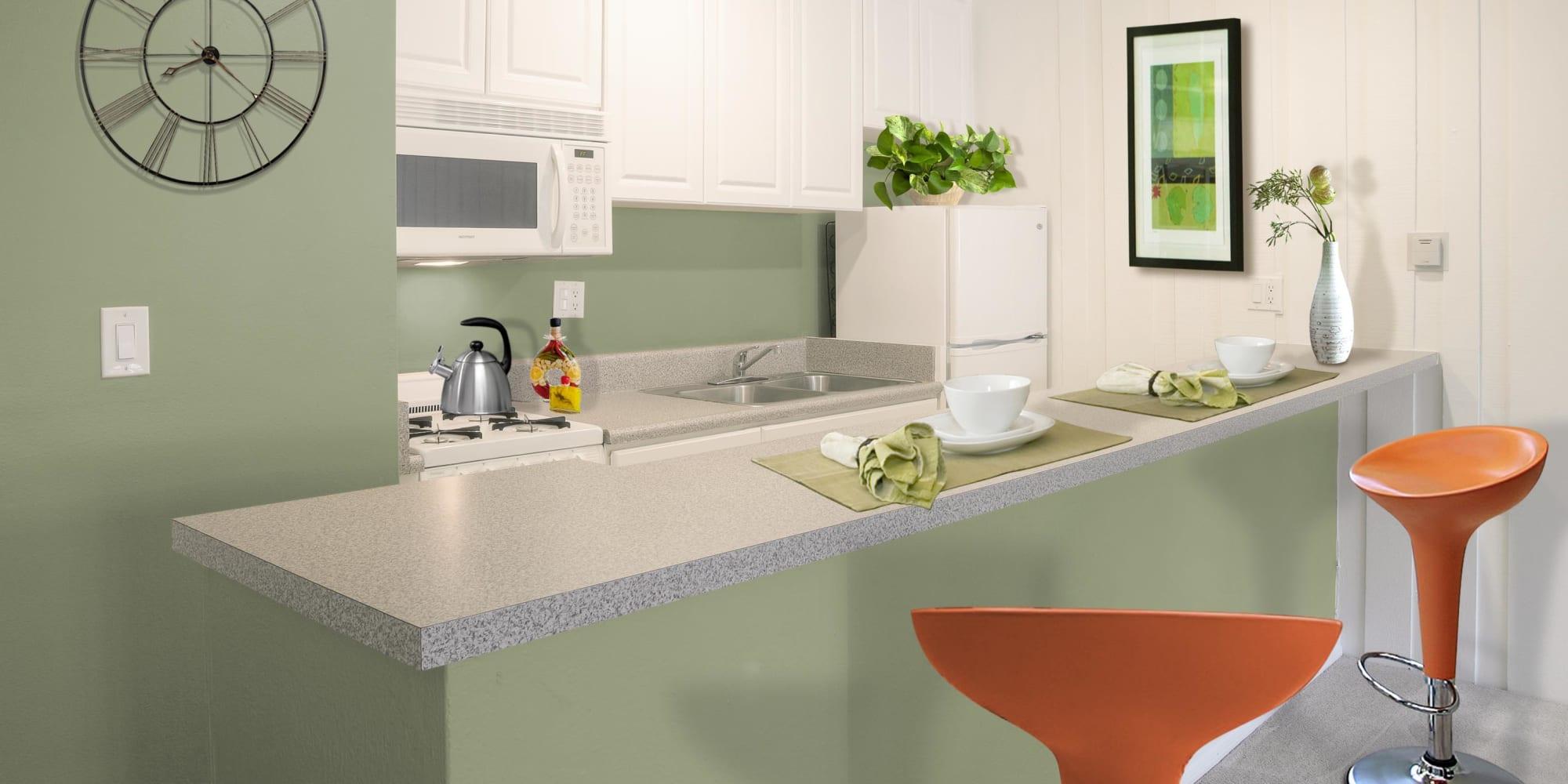 Quartz countertop and white appliances in a model apartment's kitchen at Rancho Los Feliz in Los Angeles, California