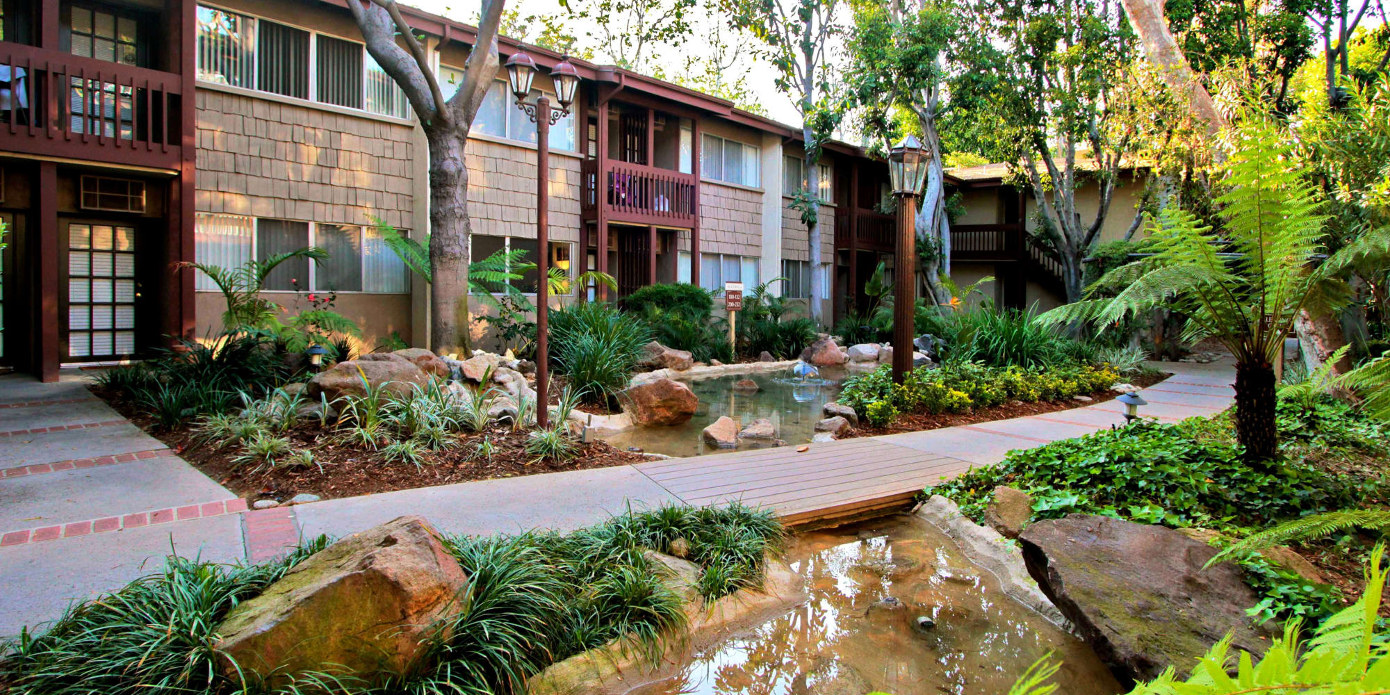 Water features and lush landscaping outside resident buildings at Rancho Los Feliz in Los Angeles, California
