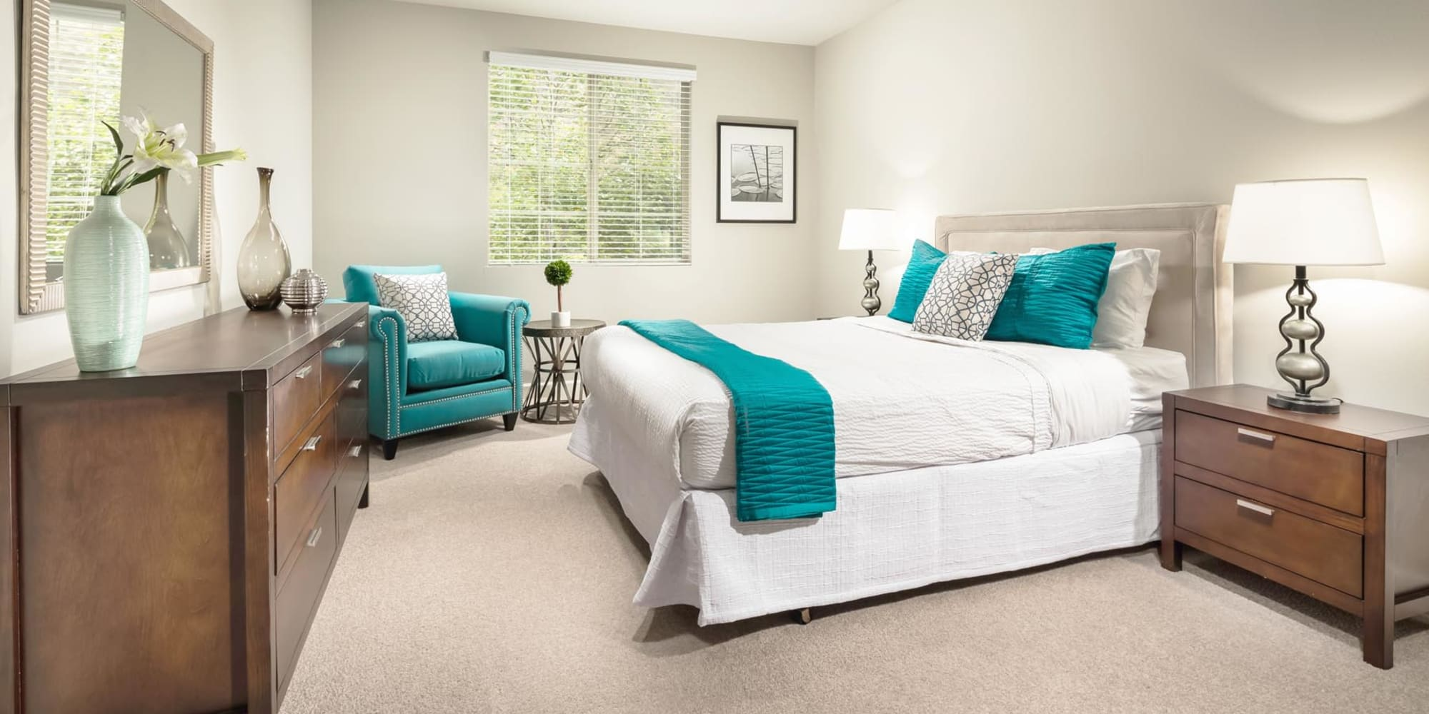 Classic furnishings and plush carpeting in a model home's primary bedroom at Mission Hills in Camarillo, California