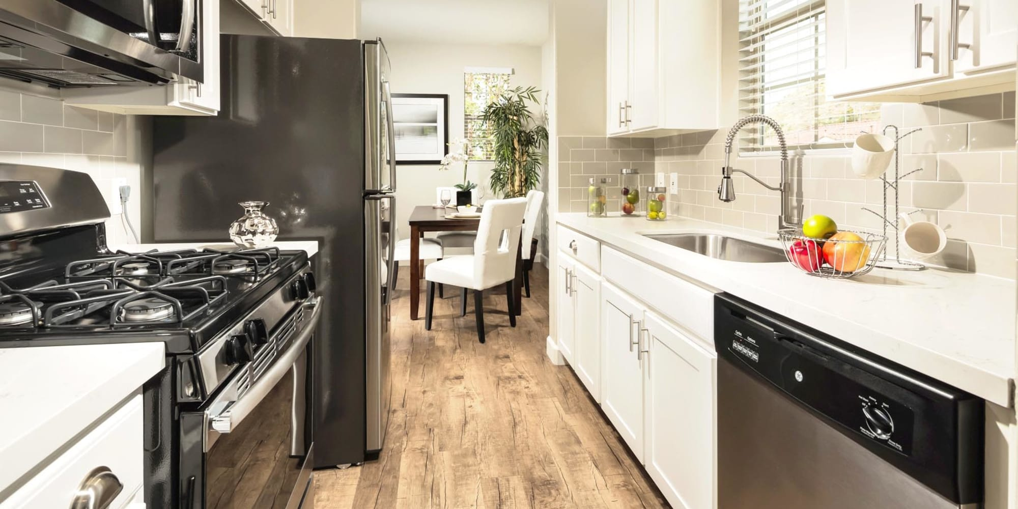 Bright white cabinetry and hardwood flooring in a model home's kitchen at Mission Hills in Camarillo, California
