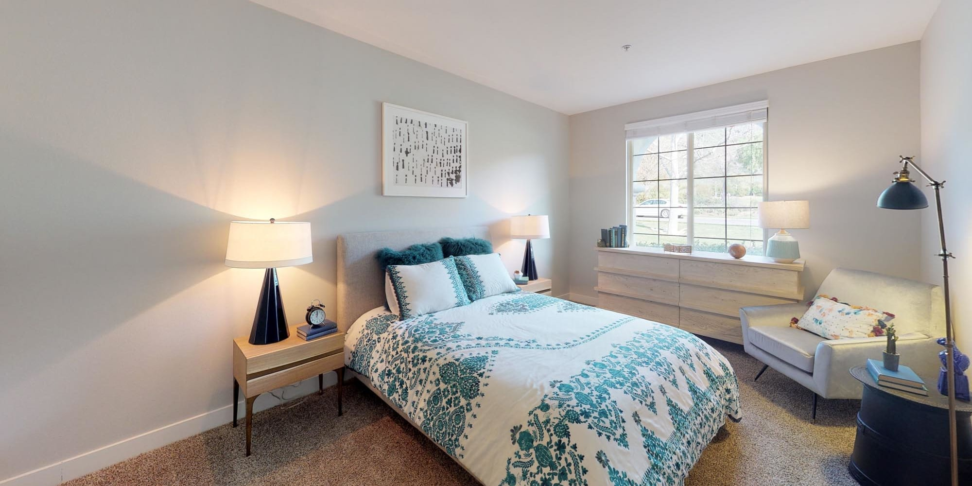 Plush carpeting and a large bay window in a model apartment's bedroom at Mission Hills in Camarillo, California