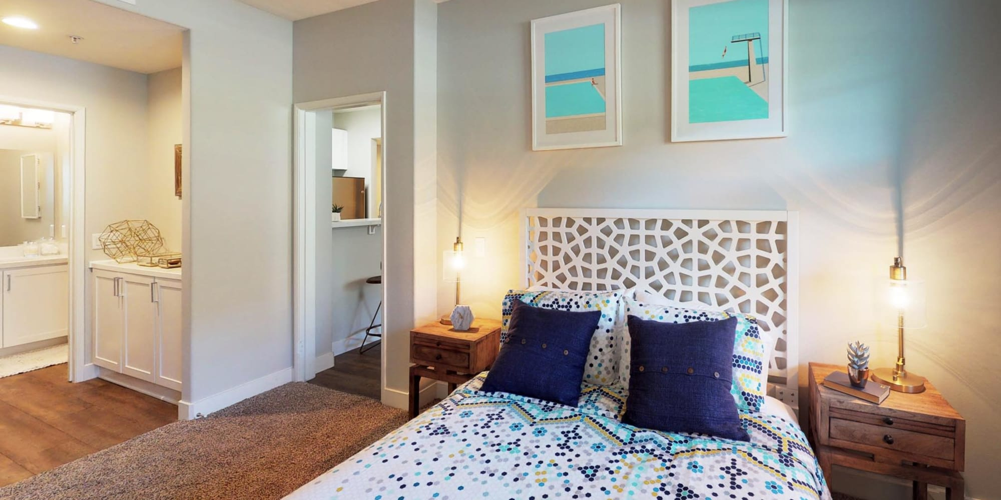 Comfortably furnished primary bedroom with an en suite bathroom in a model home at Mission Hills in Camarillo, California