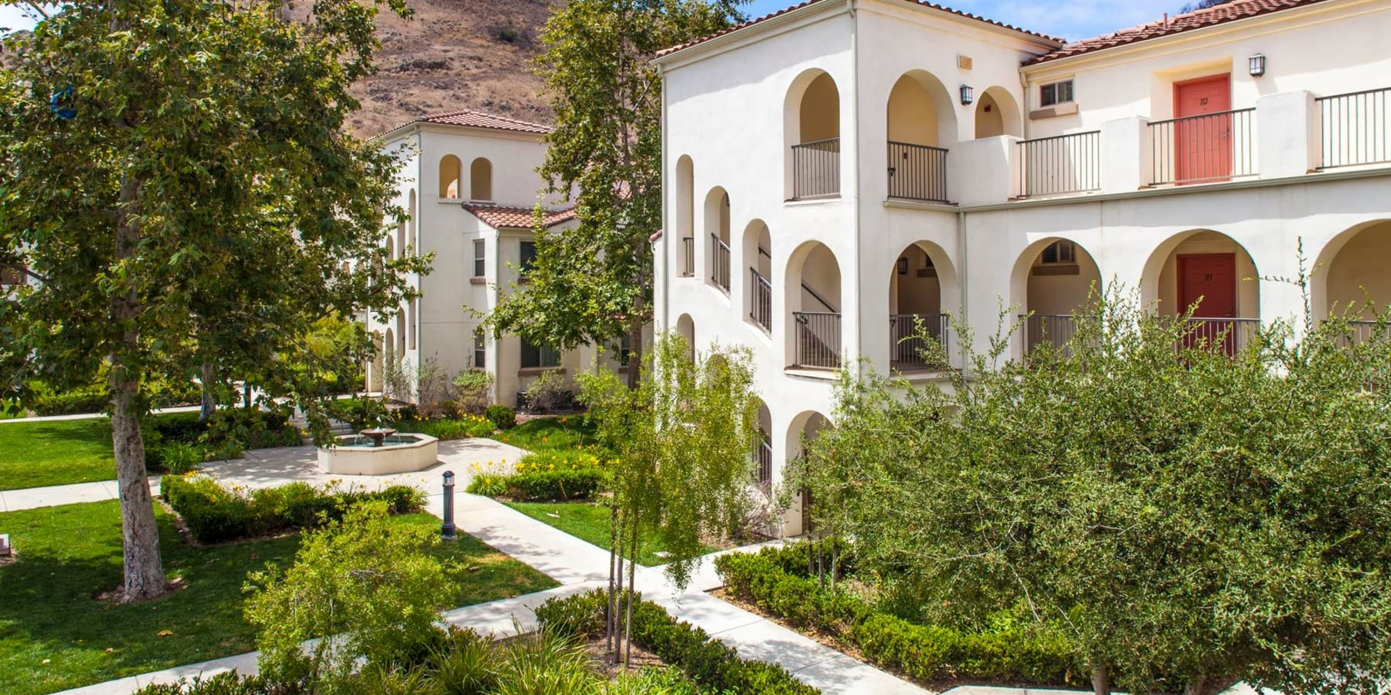 Lush landscaping and mature trees throughout our mission-style community at Mission Hills in Camarillo, California