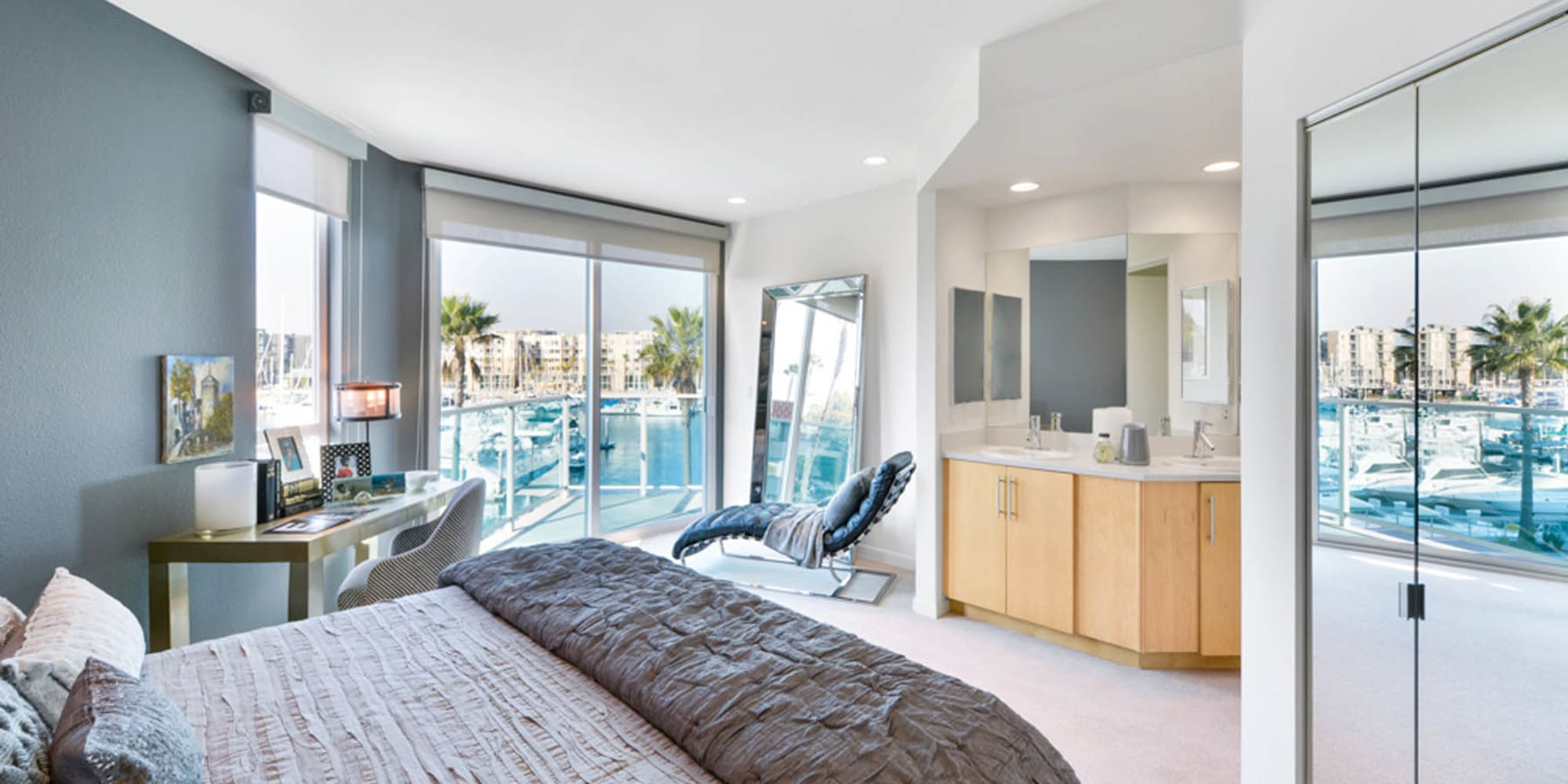 Floor-to-ceiling windows and plush carpeting in the primary bedroom of model luxury apartment at Esprit Marina del Rey in Marina Del Rey, California