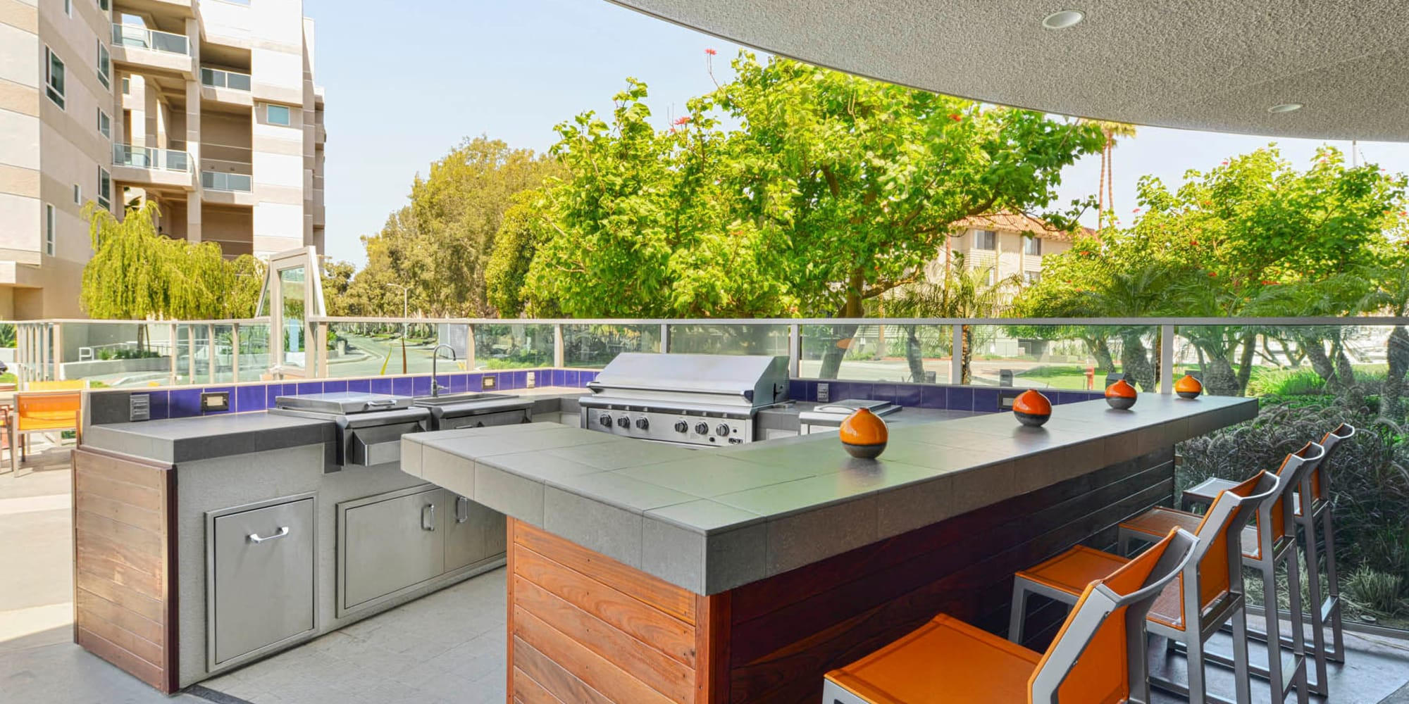 Outdoor kitchen with gas barbecue grills and bar seating at Esprit Marina del Rey in Marina Del Rey, California
