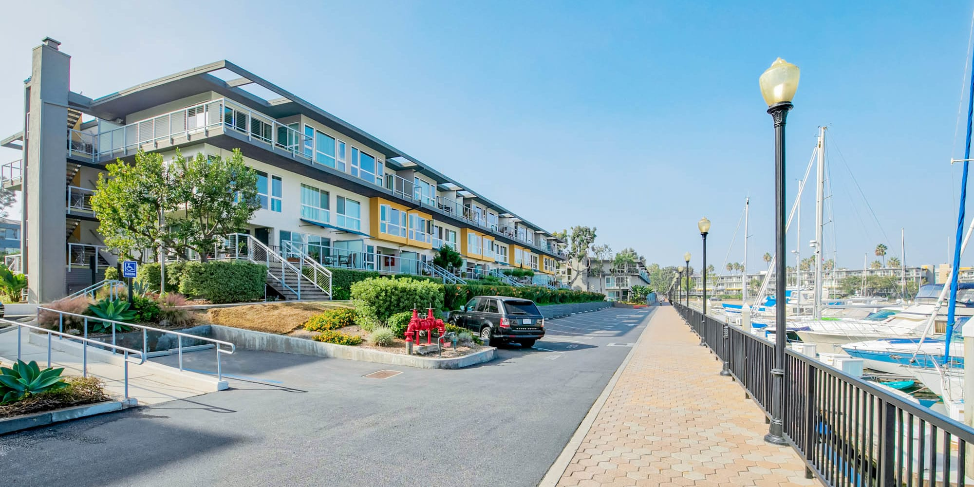 Paved drive between resident buildings and the boardwalk overlooking the marina at The Tides at Marina Harbor in Marina Del Rey, California