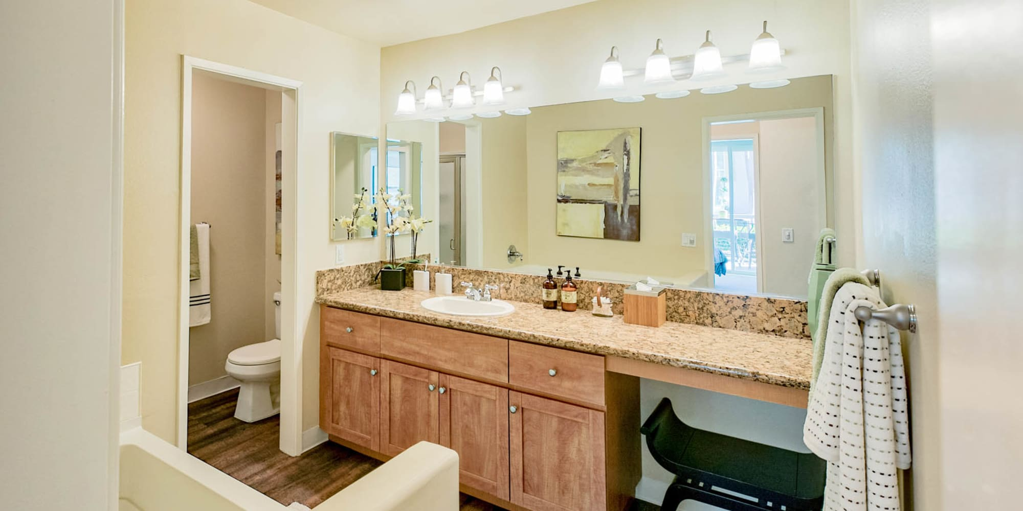 Large vanity mirror and a granite countertop in a model home's bathroom at Waters Edge at Marina Harbor in Marina Del Rey, California