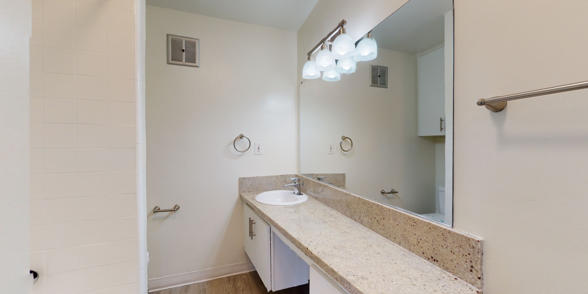 Classic apartment's bathroom with a granite countertop at Sunset Barrington Gardens in Los Angeles, California