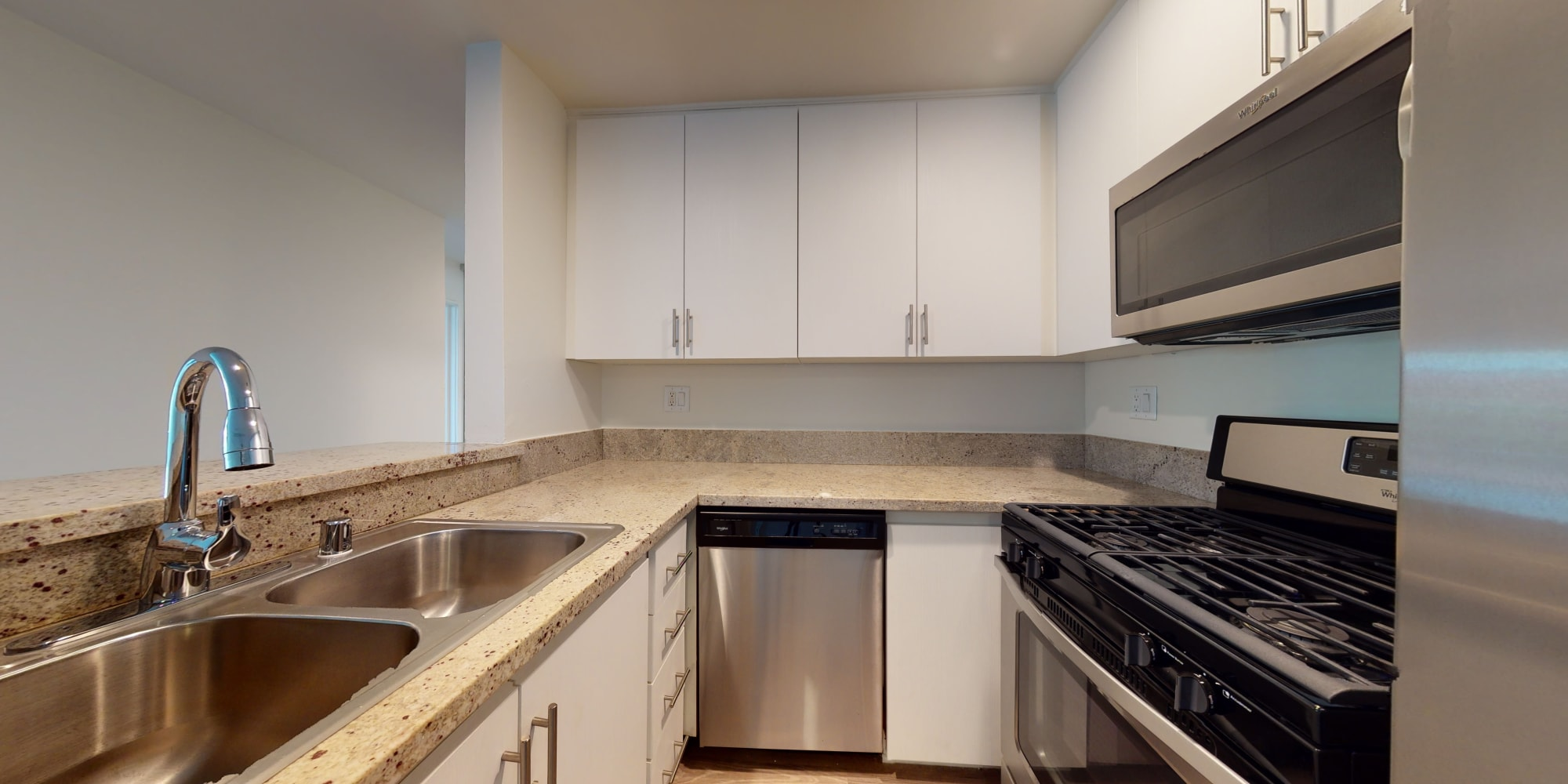 Classic apartment's kitchen with stainless-steel appliances and a dual-basin sink at Sunset Barrington Gardens in Los Angeles, California
