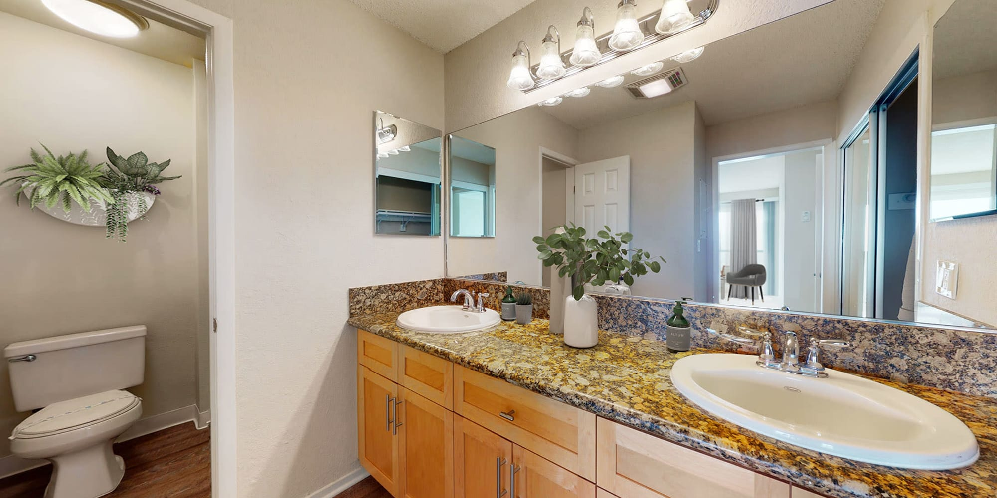 Bathroom with granite countertops and double sinks in a spacious apartment home at The Tides at Marina Harbor in Marina del Rey, California