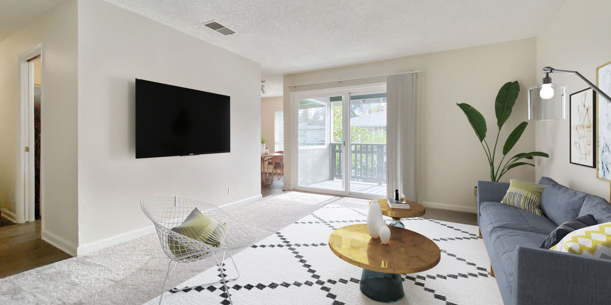 Modern furnishings and a wall-mounted flatscreen TV in a model apartment's living area at Pleasanton Glen Apartment Homes in Pleasanton, California
